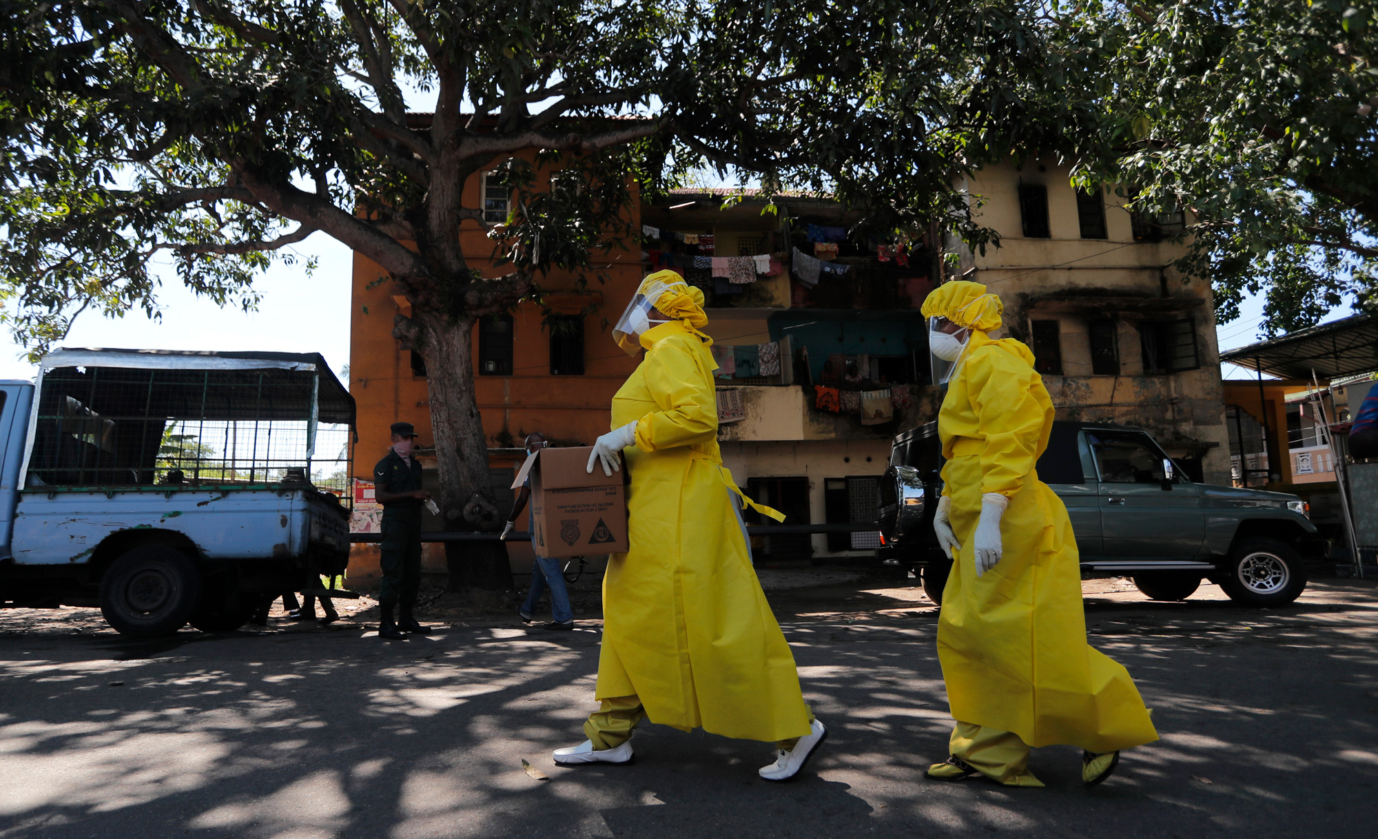 Medical workers garbed in protective gear walk through a neighborhood in Columbo, Sri Lanka.