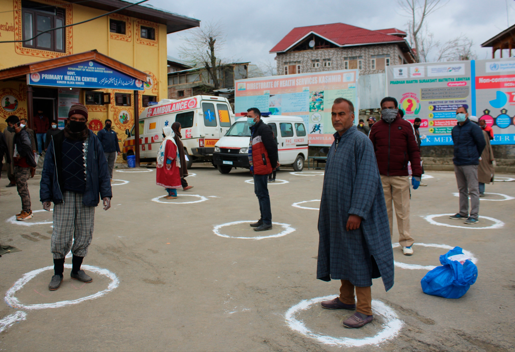 In the street outside a hospital in Srinigar, people wait in small circles marked on the street to stay separated.