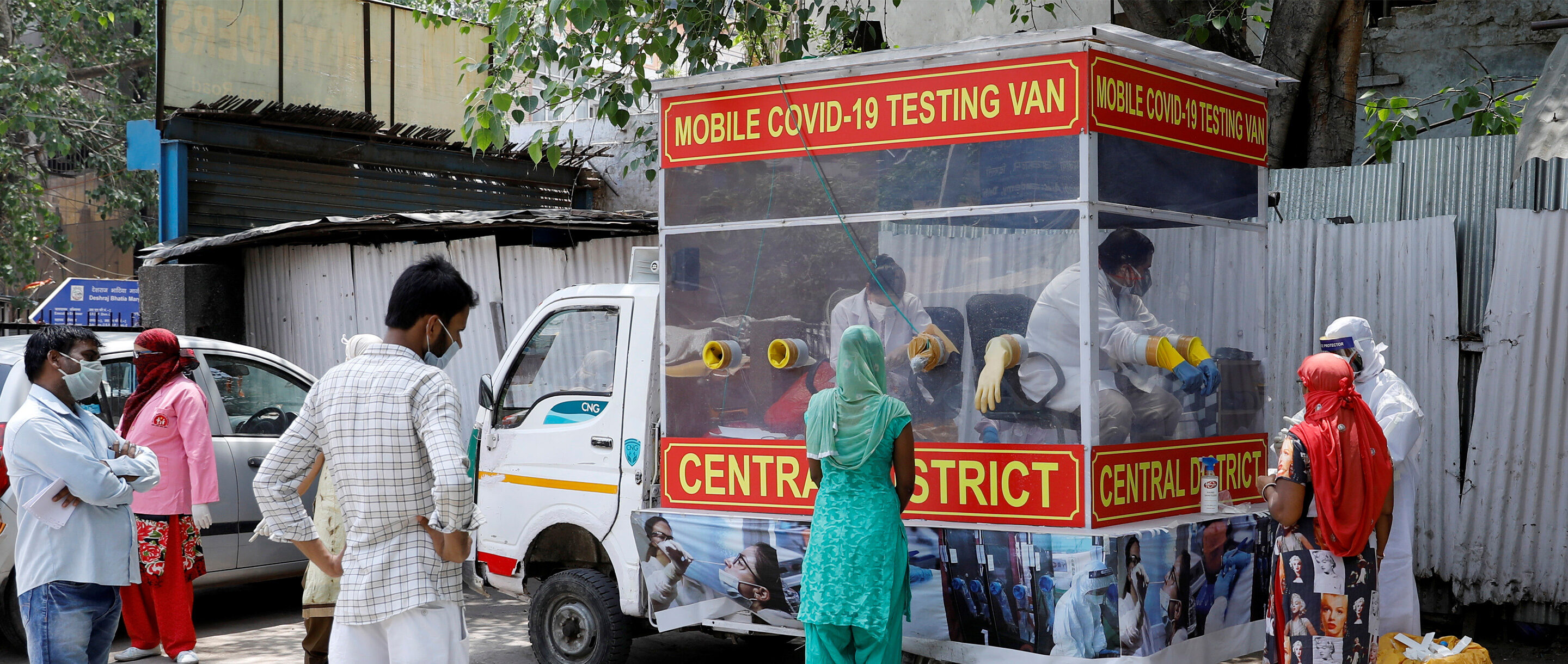 People in India stand near a red van that serves as a mobile testing center for COVID-19 .