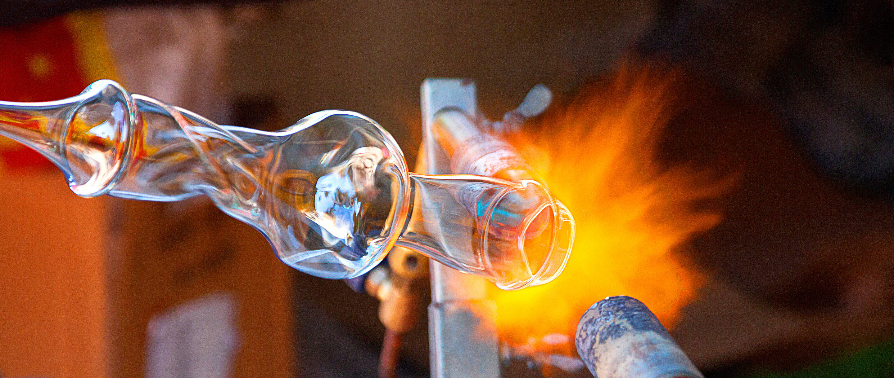 A glass object being shaped by a blowtorch.]