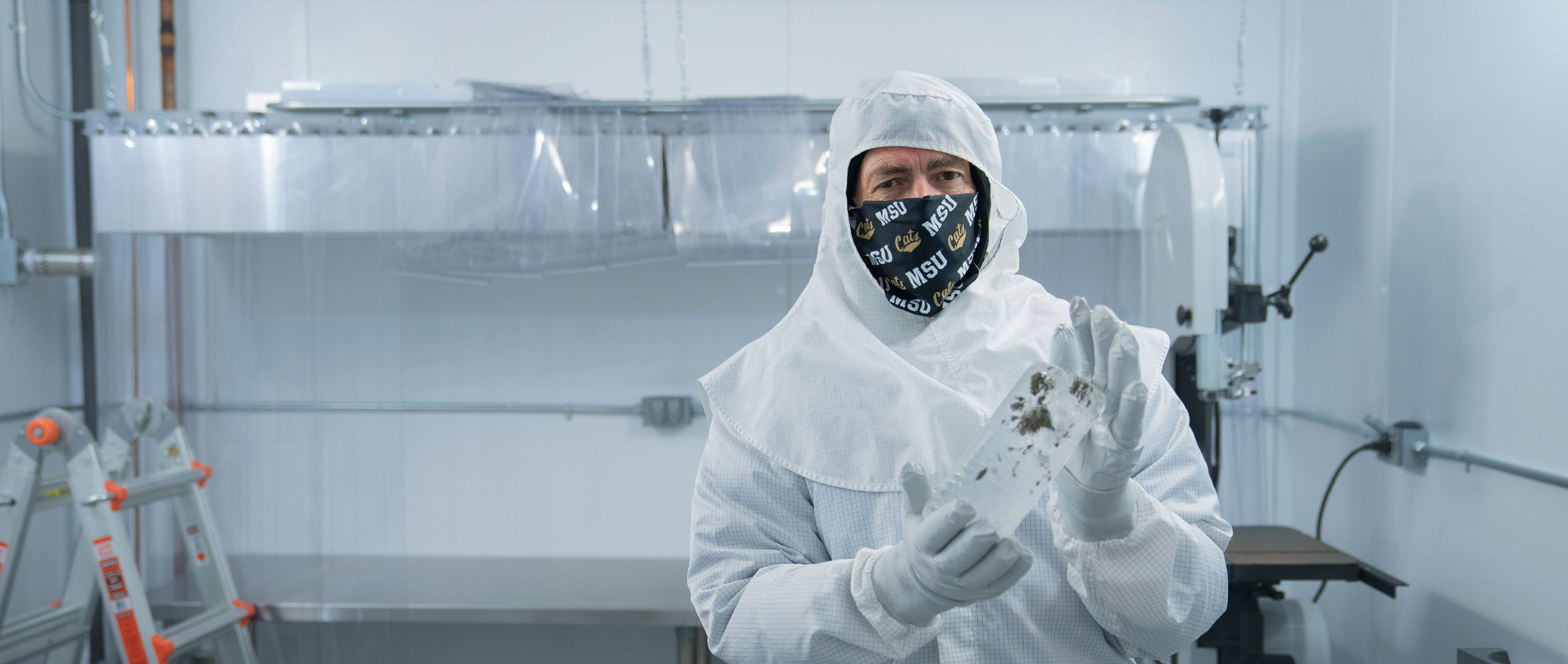 John Priscu holds an ice core sample in a sterile laboratory.
