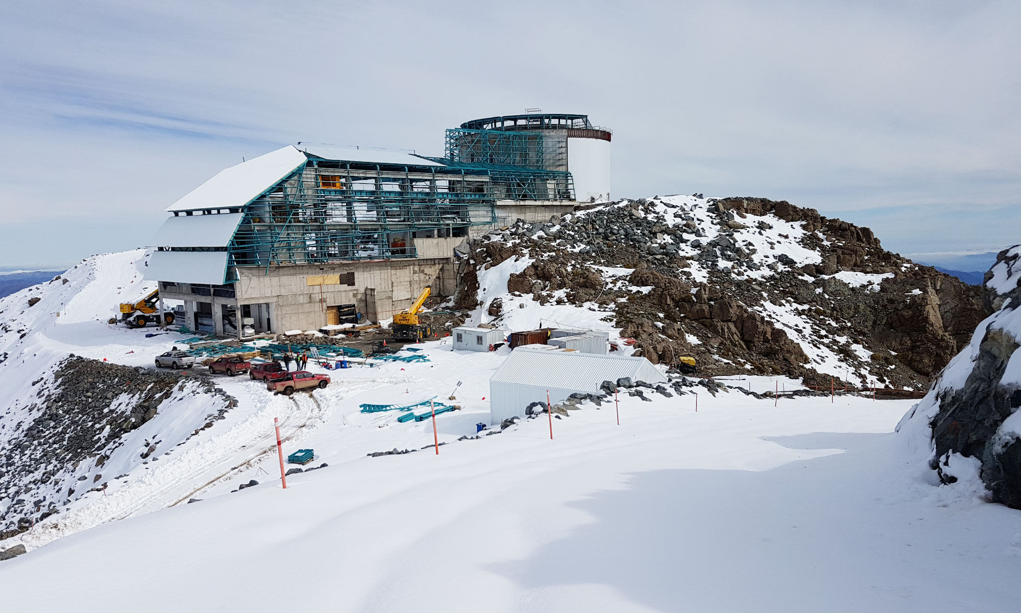 Photo of the Vera C. Rubin Observatory under construction on a snowy mountaintop.