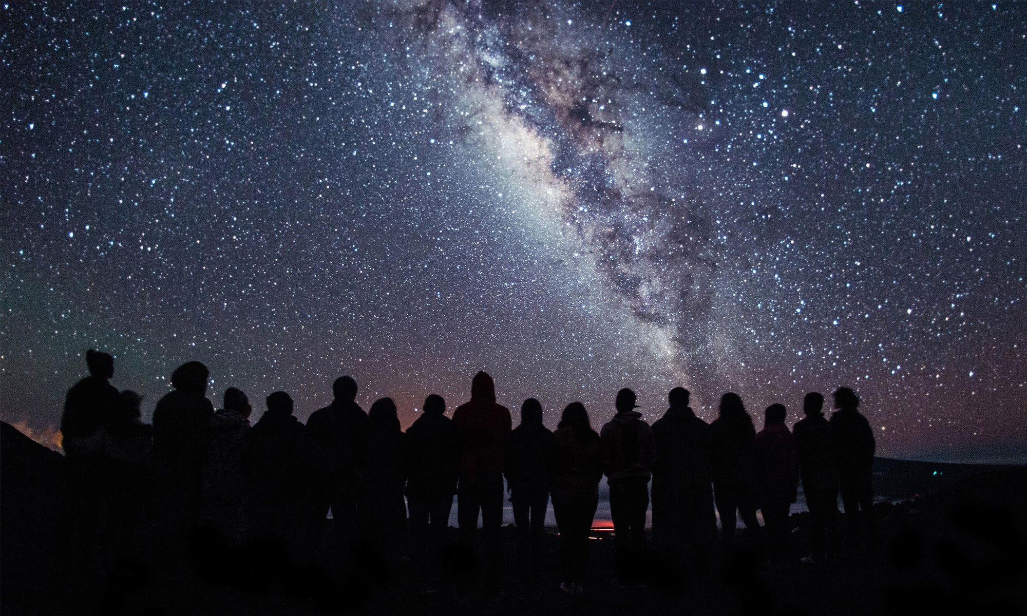 Photo of a group of people silhouetted against the Milky Way.