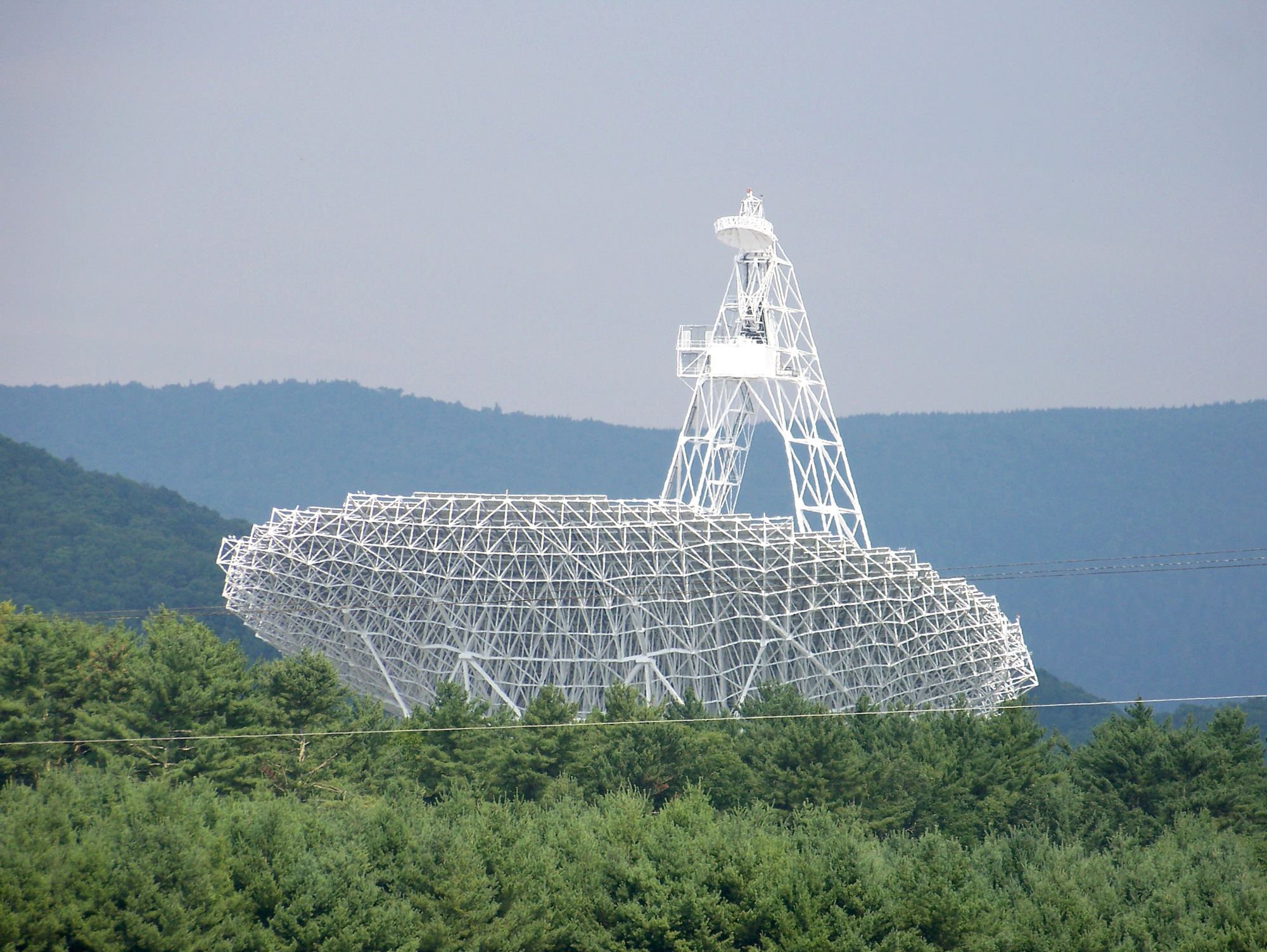 The large dish of a radio telescope pointed toward the sky against a forest landscape.