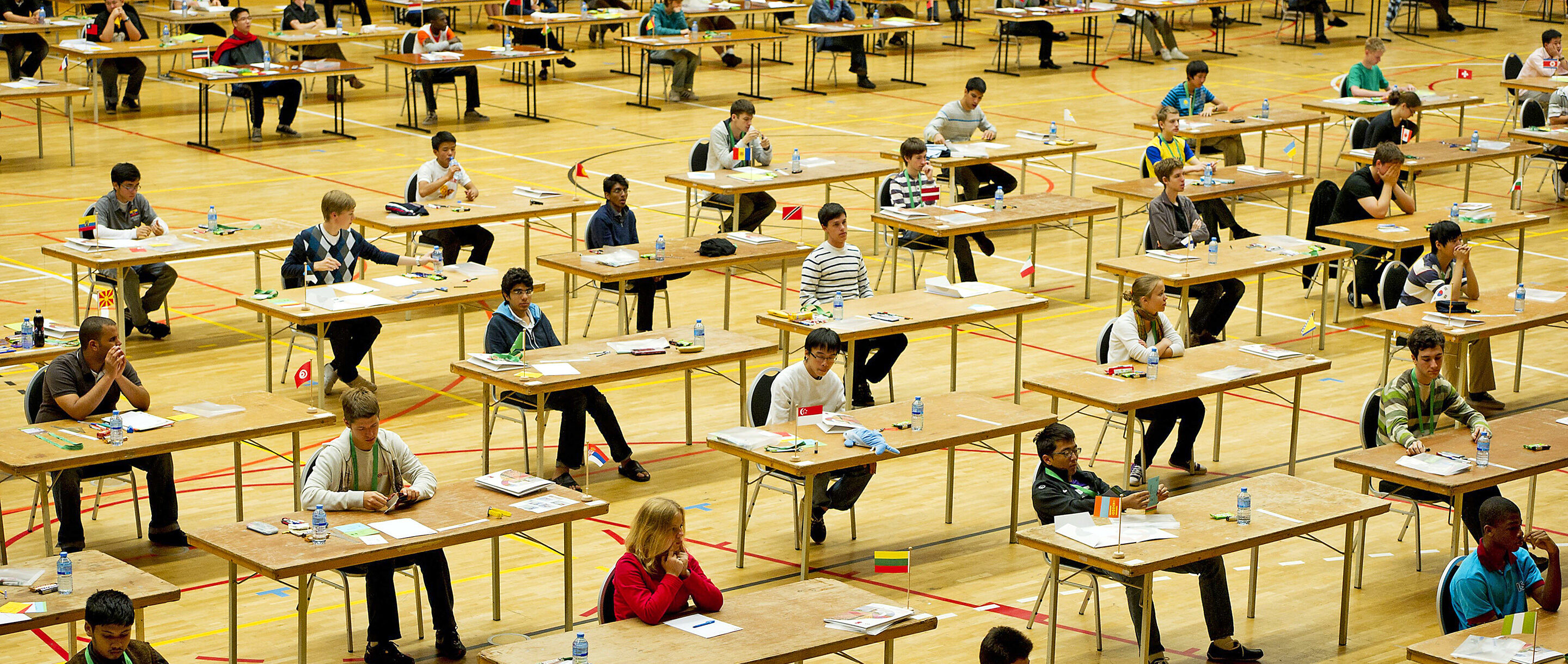 Photo of students sitting at desks competing in the International Mathematical Olympiad