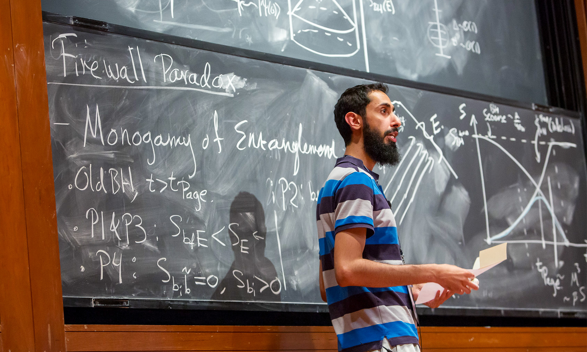 Ahmed Almheiri lecturing about the firewall paradox in front of a blackboard.