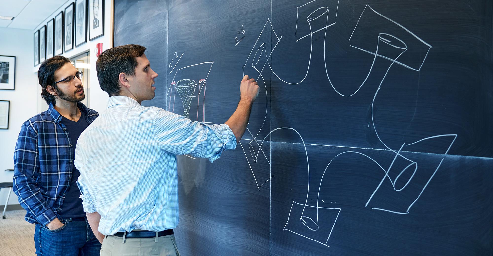 Tom Hartman and Amirhossein Tajdi at a chalkboard.