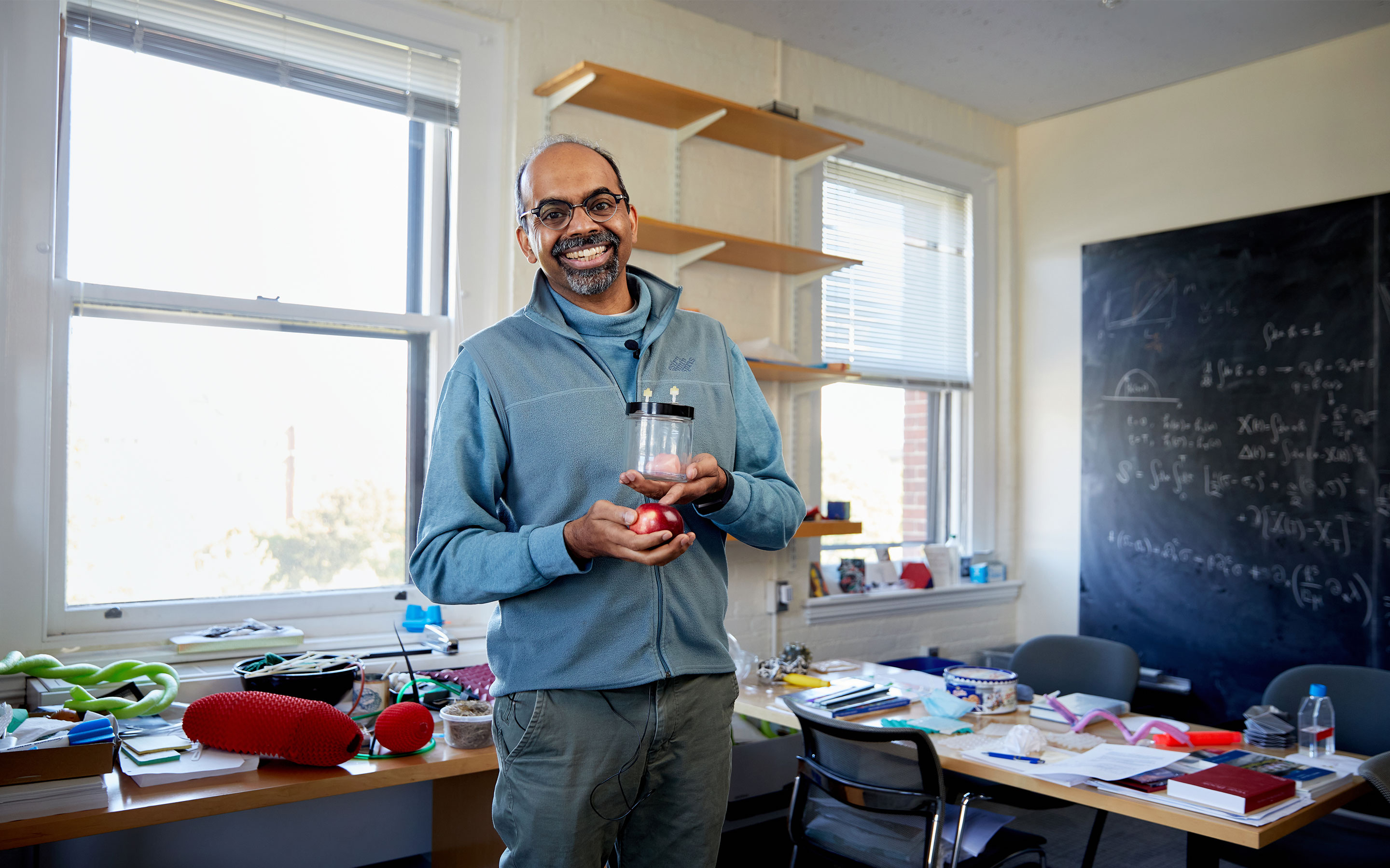 Harvard professor L. Mahadevan stands in a slightly cluttered office, holding an apple and a jar containing a miniature brain