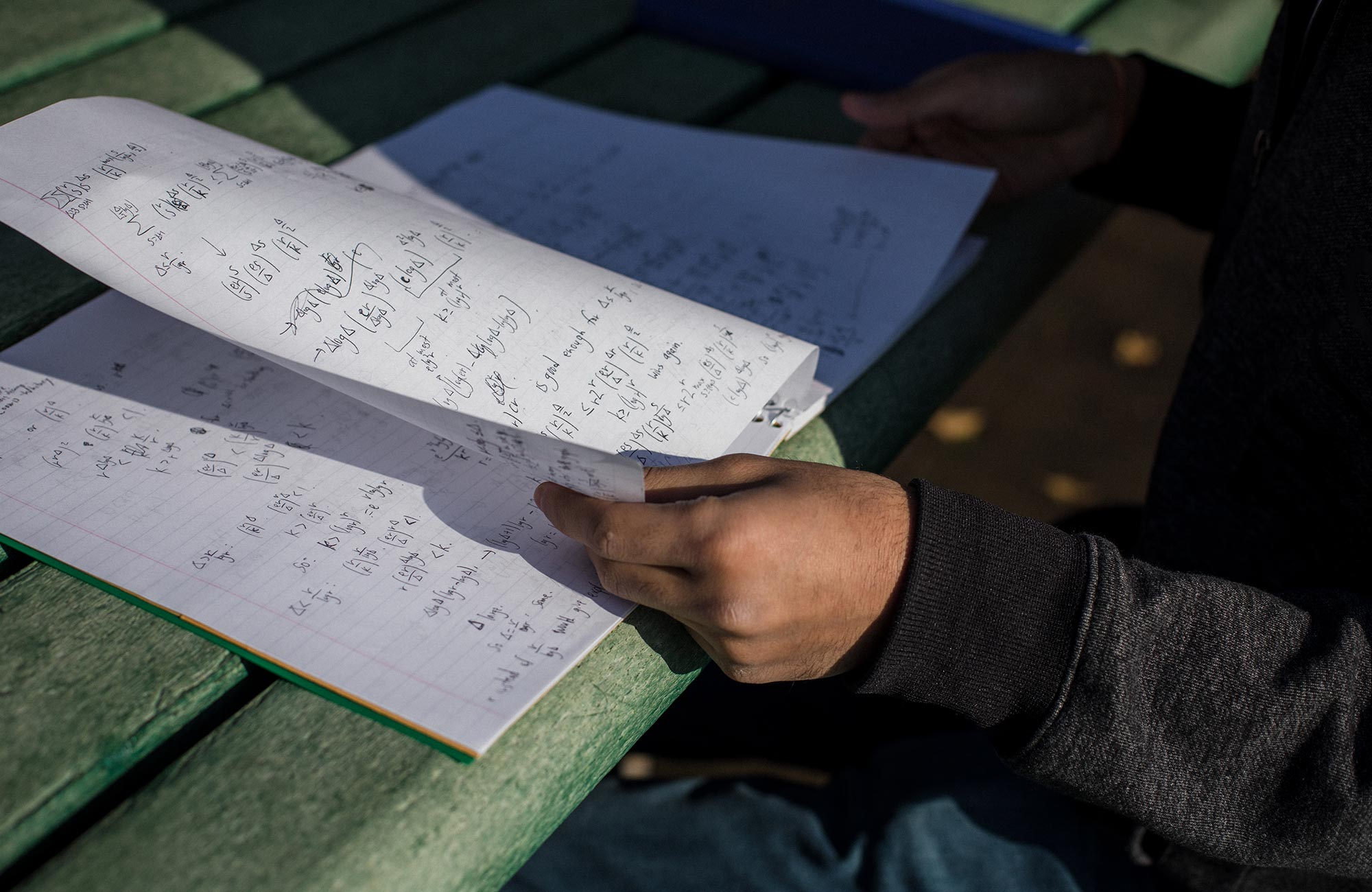 A photo of Ashwin Sah working at a park table, and a photo of his notebook