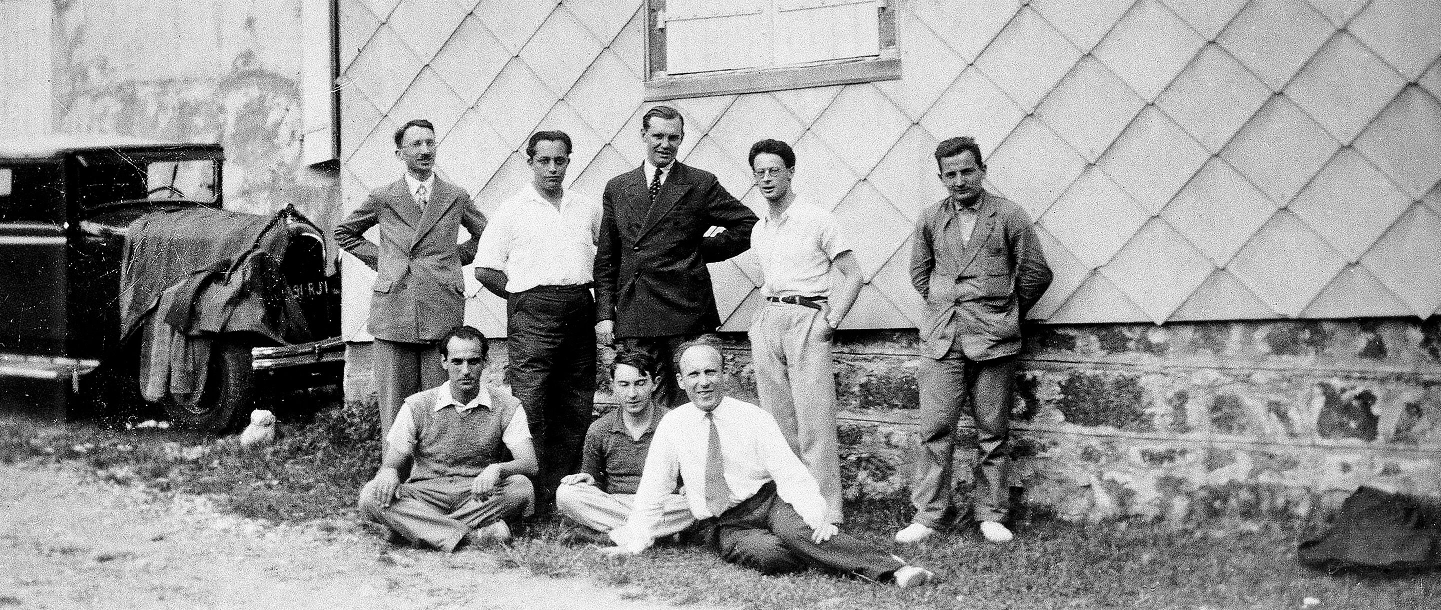 Black and white historical photo of eight men in front of a building, including Henri Cartan, André Weil and Szolem Mandelbrojt.