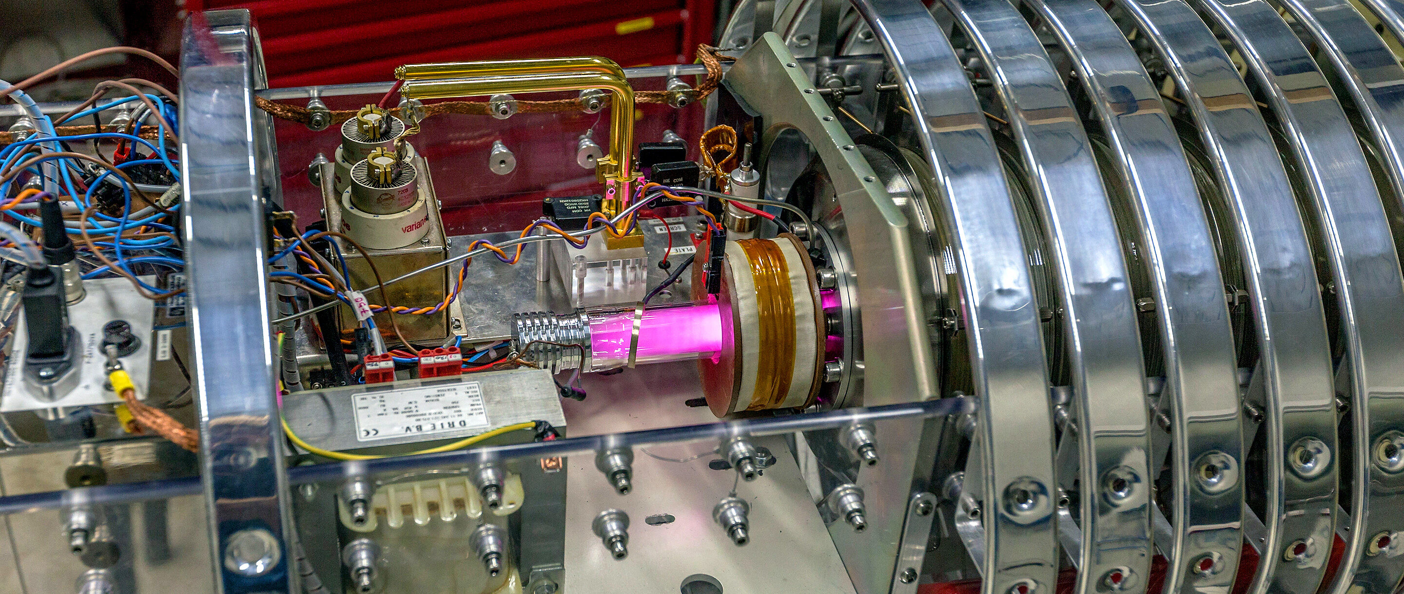 A pink beam at the center of a metallic experimental apparatus.