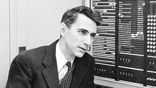 Black and white photo of Claude Shannon in front of a computer