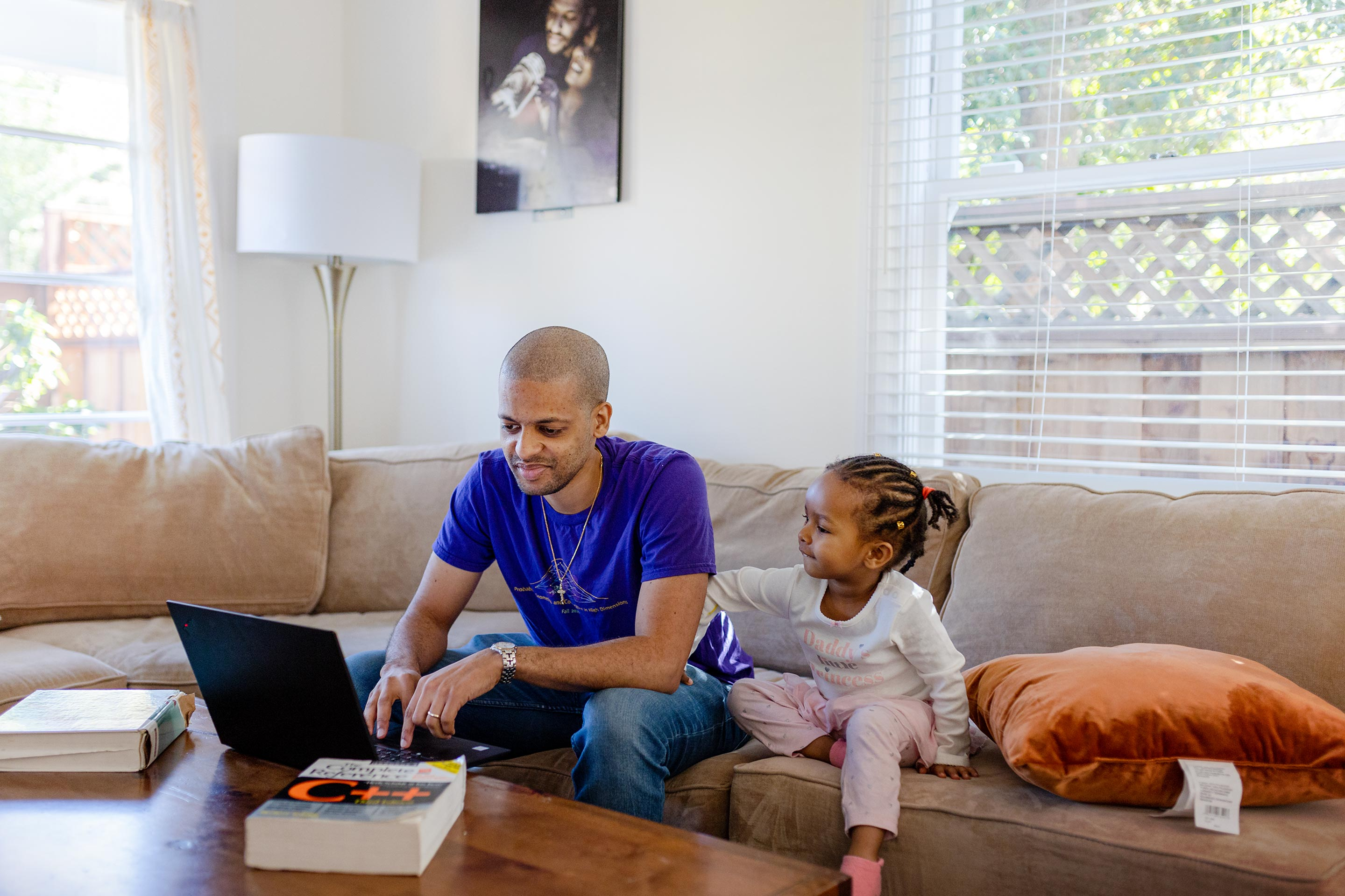 Computer scientist Jelani Nelson seated on a couch next to his daughter. There are textbooks and a laptop on the coffee table in front of him.