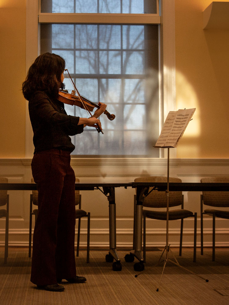 A diptych. On left, Lauren Williams standing and playing the violin in front of sheet music. On the right, Williams playing the violin as a child.