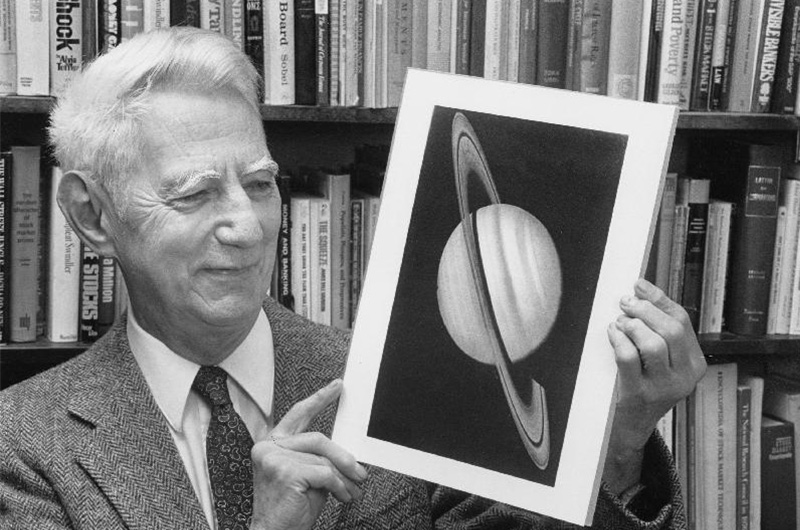 A black and white photo of an older Claude Shannon looking at a photo of Saturn