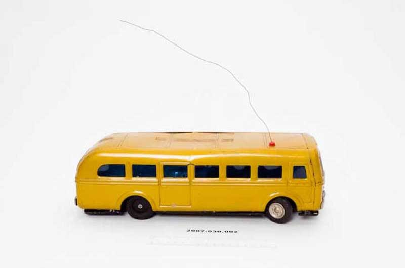 a closeup photo of a remote-controlled yellow bus he built