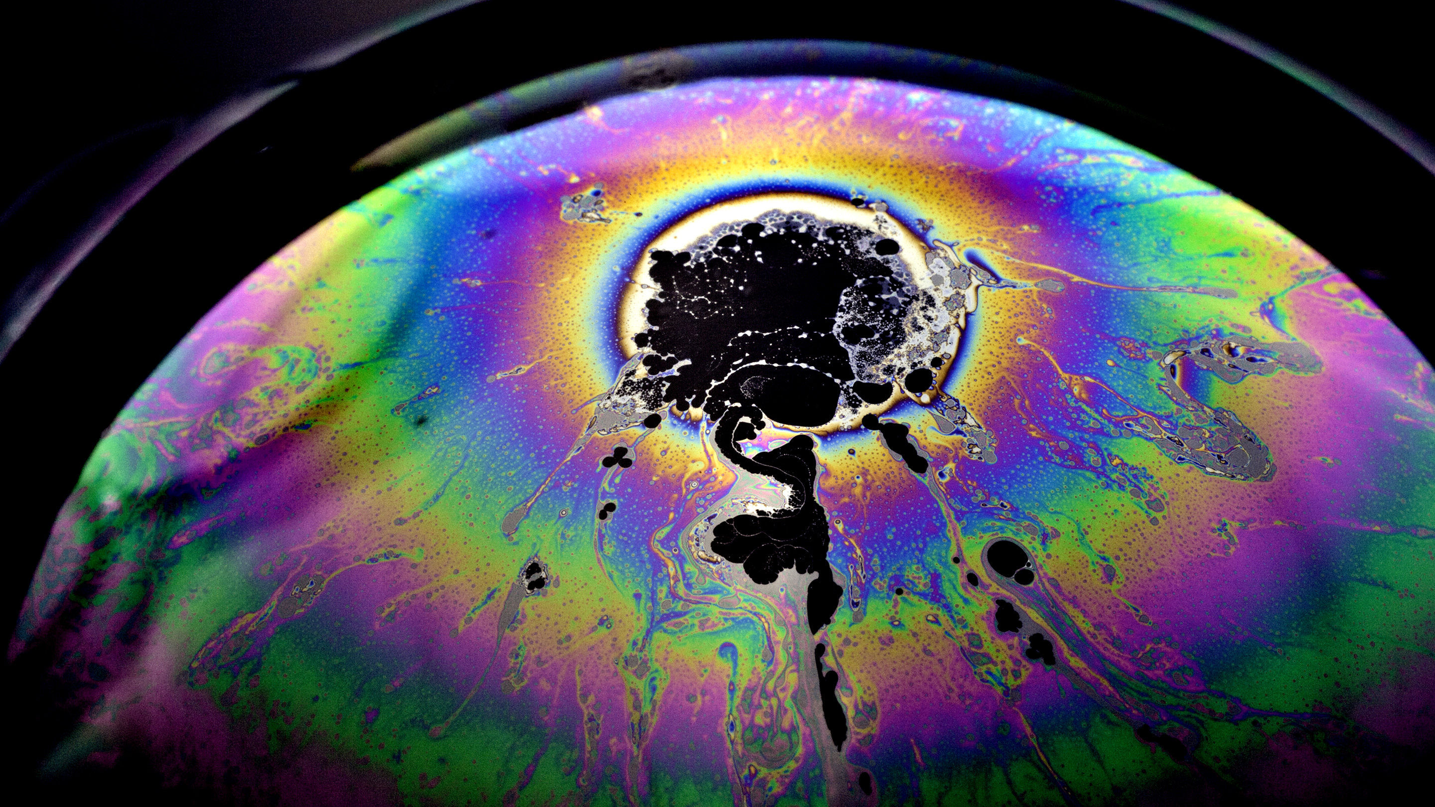 Close-up photograph of a soap bubble with a spot on it that looks as though it must have come from a collision.