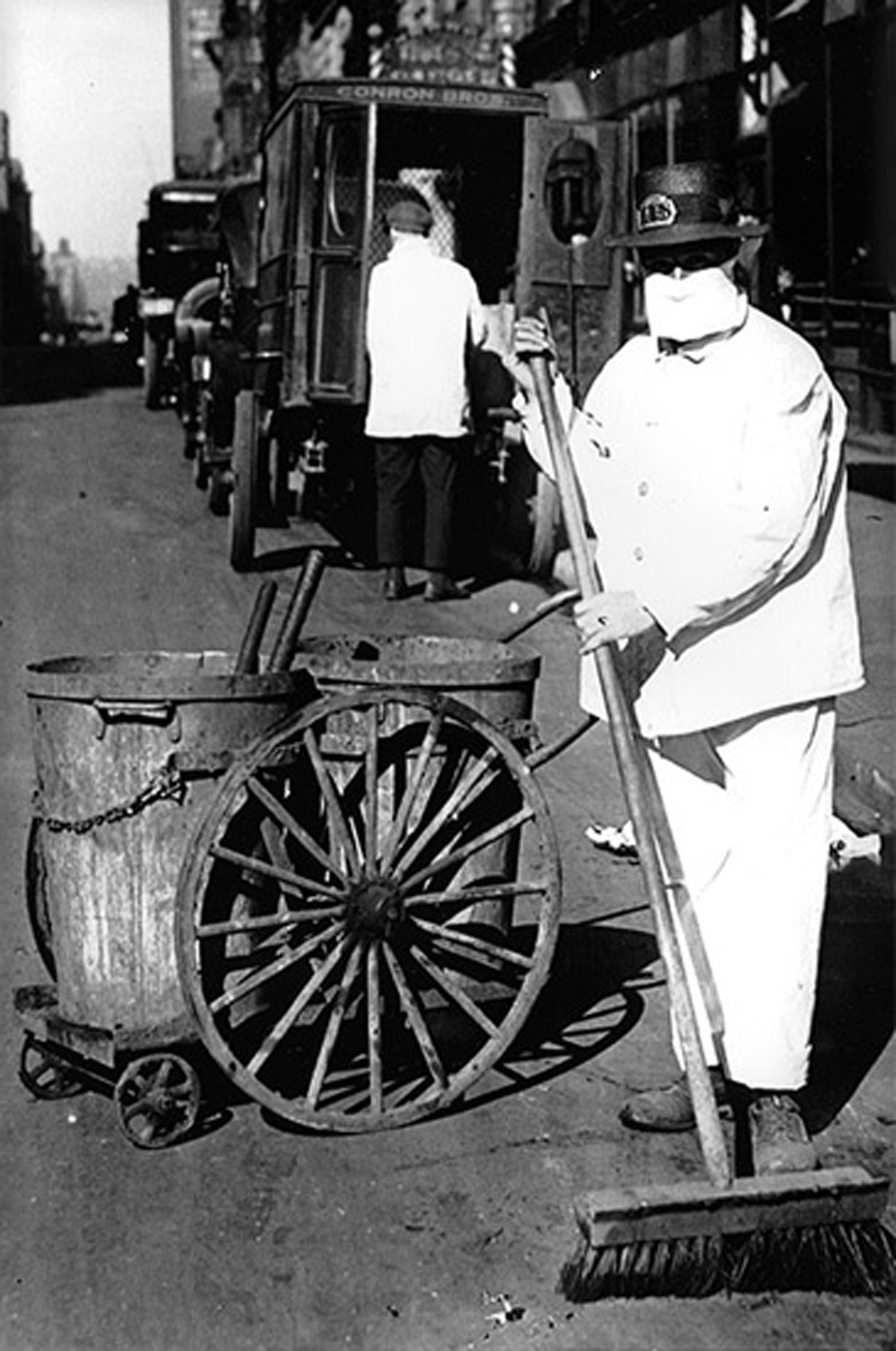 Two photos from the 1918 influenza pandemic: a poster warning people to stay home and a street sweeper in a mask.