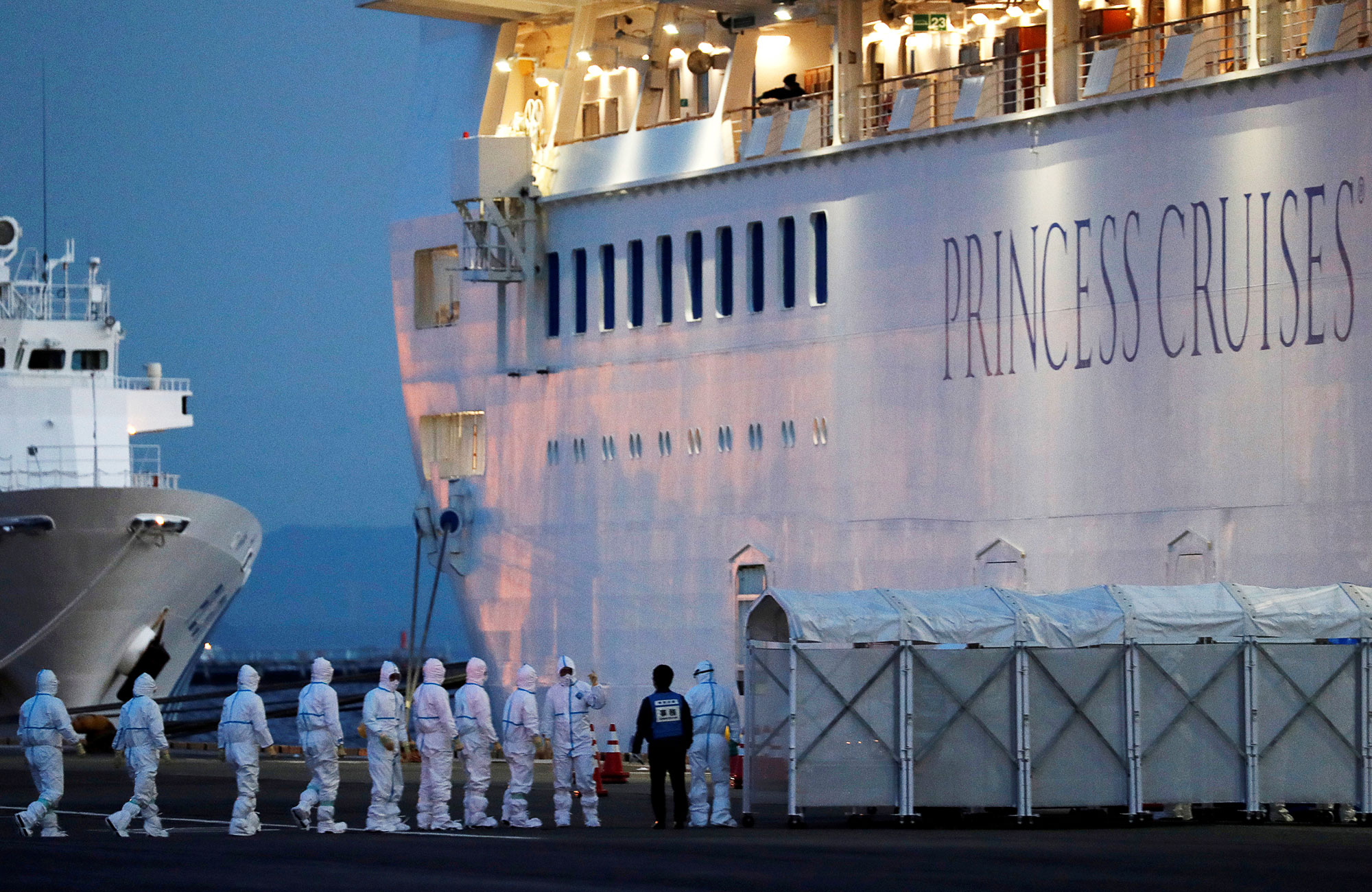 The Diamond Princess cruise ship in port, being boarded by a line of people in full protective gear.