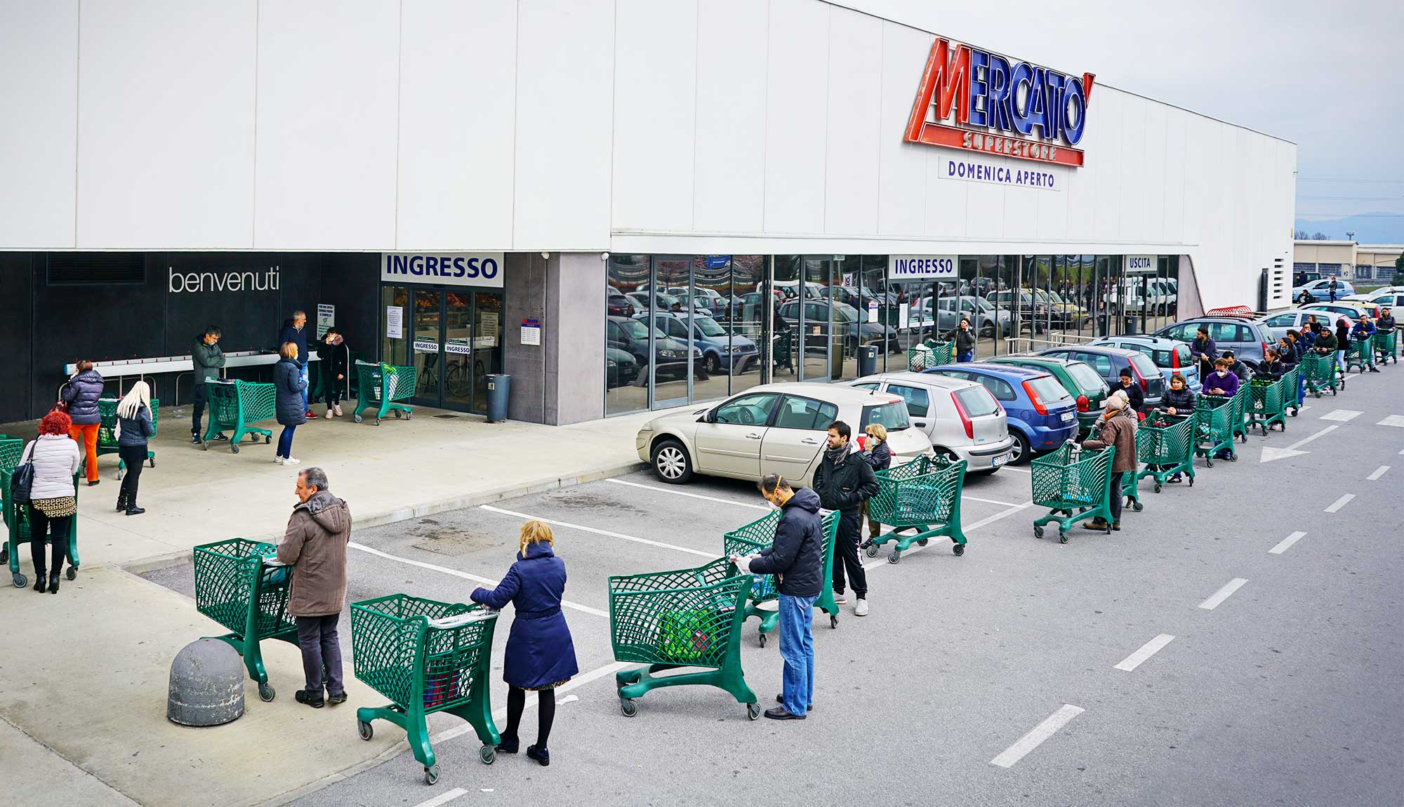Shoppers with carts wait in a socially distanced line outside a store in Milan.