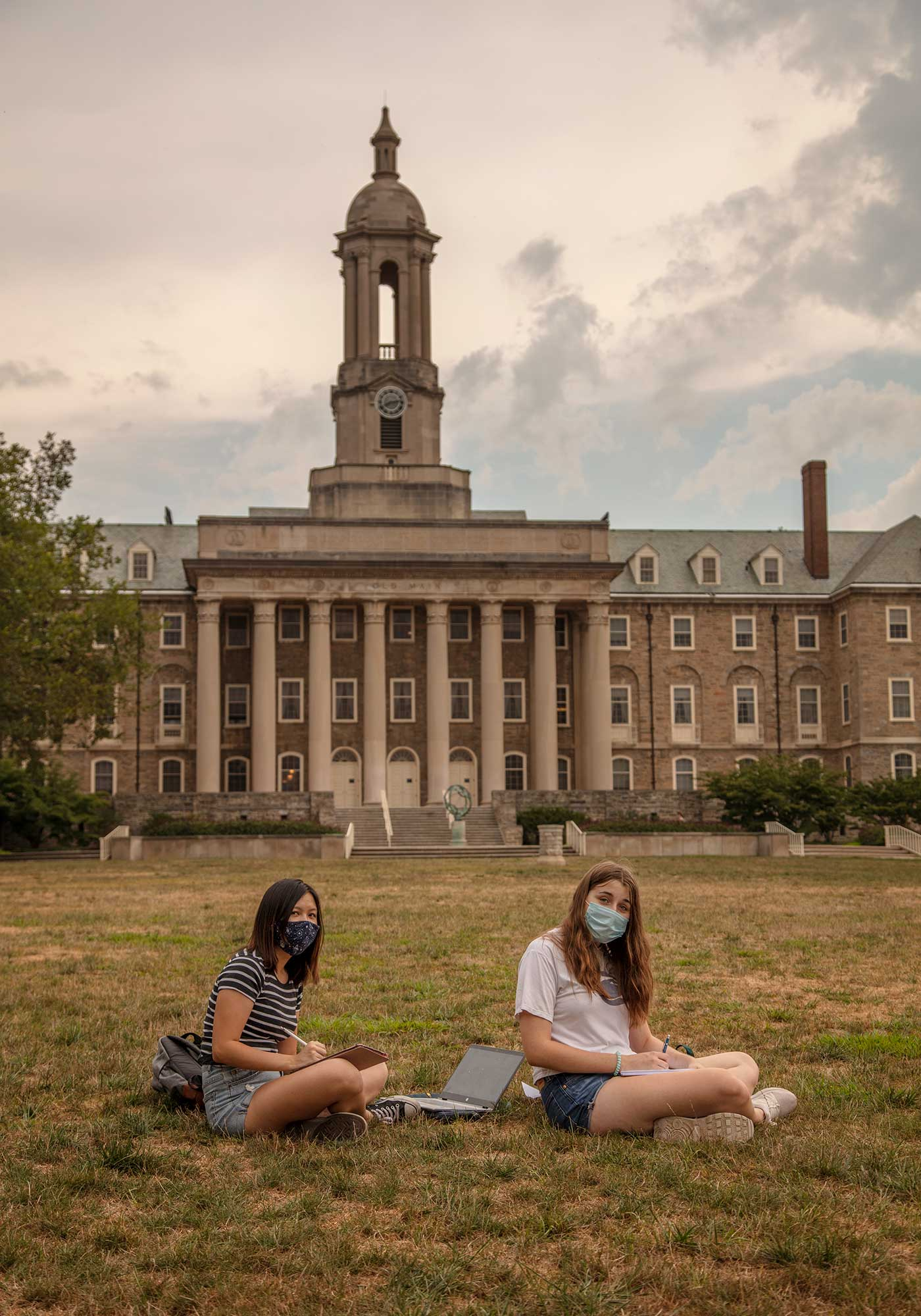 Two students wearing masks sit on a lawn at Pennsylvania State University.