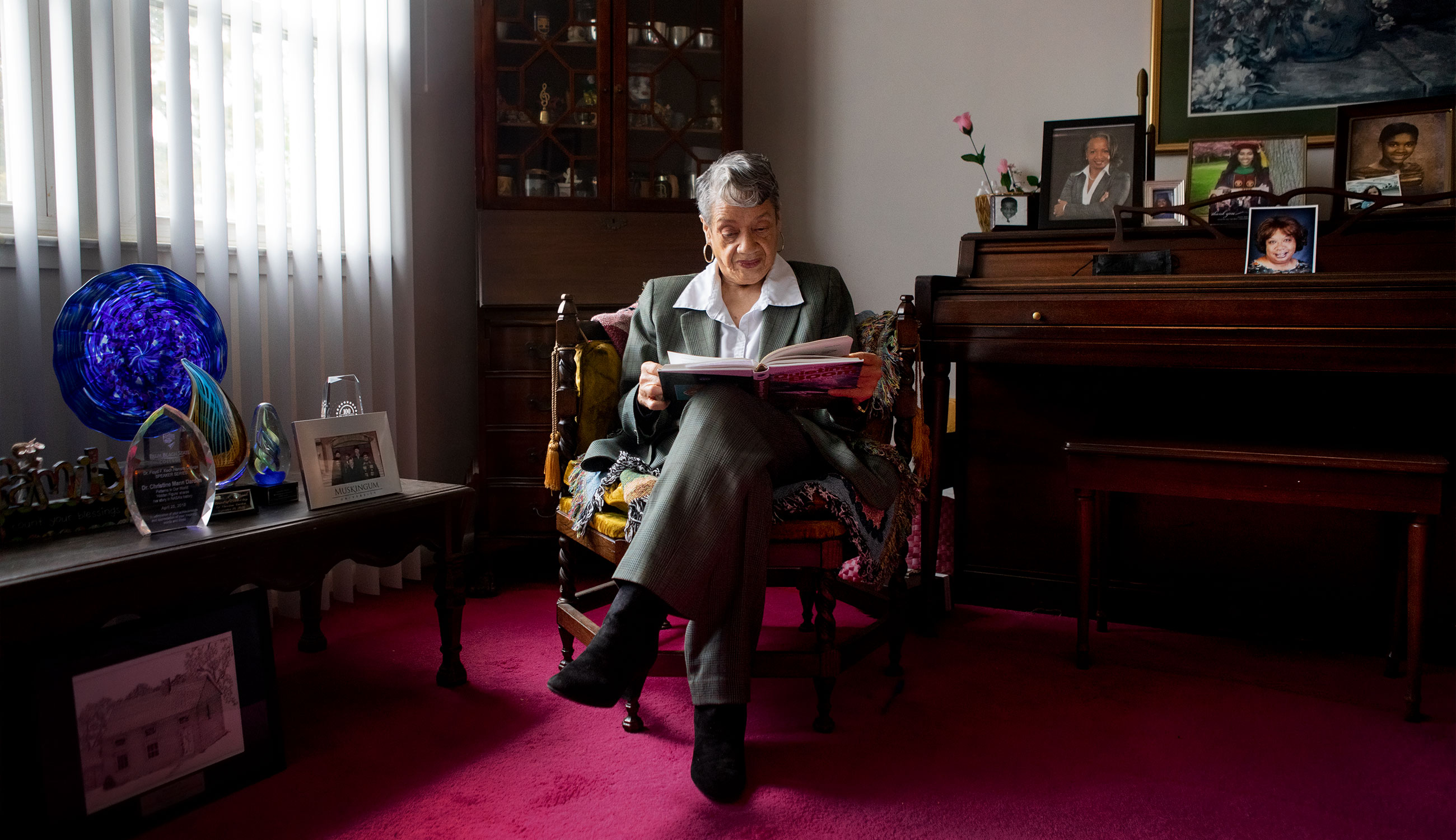 Photo of Christine Darden in a gray suit, seated reading a book in her home