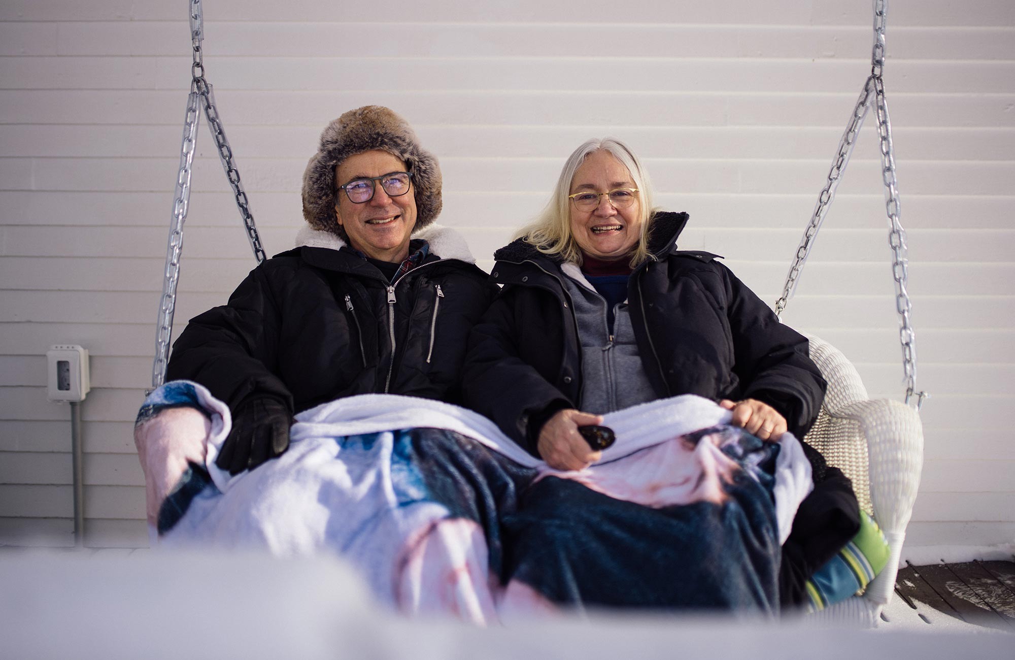 Frank Wilczek and his wife Betsy Devine sitting on a porch swing.