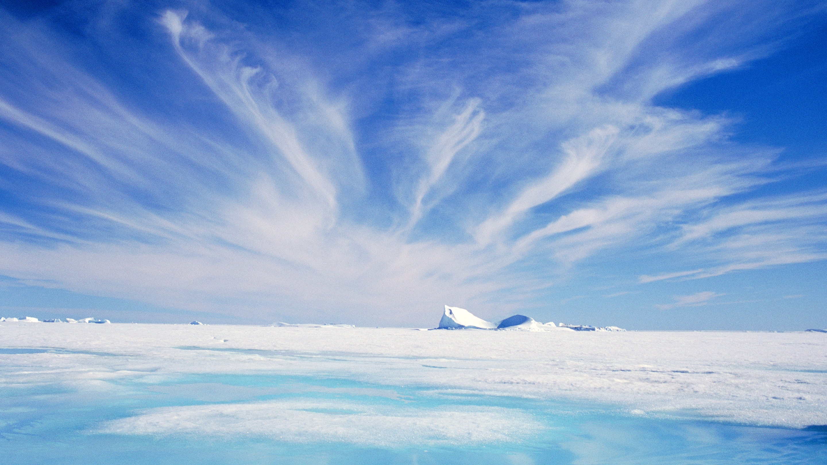 Photograph showing cirrus clouds in a blue sky above an expanse of flat, snow-covered ice.
