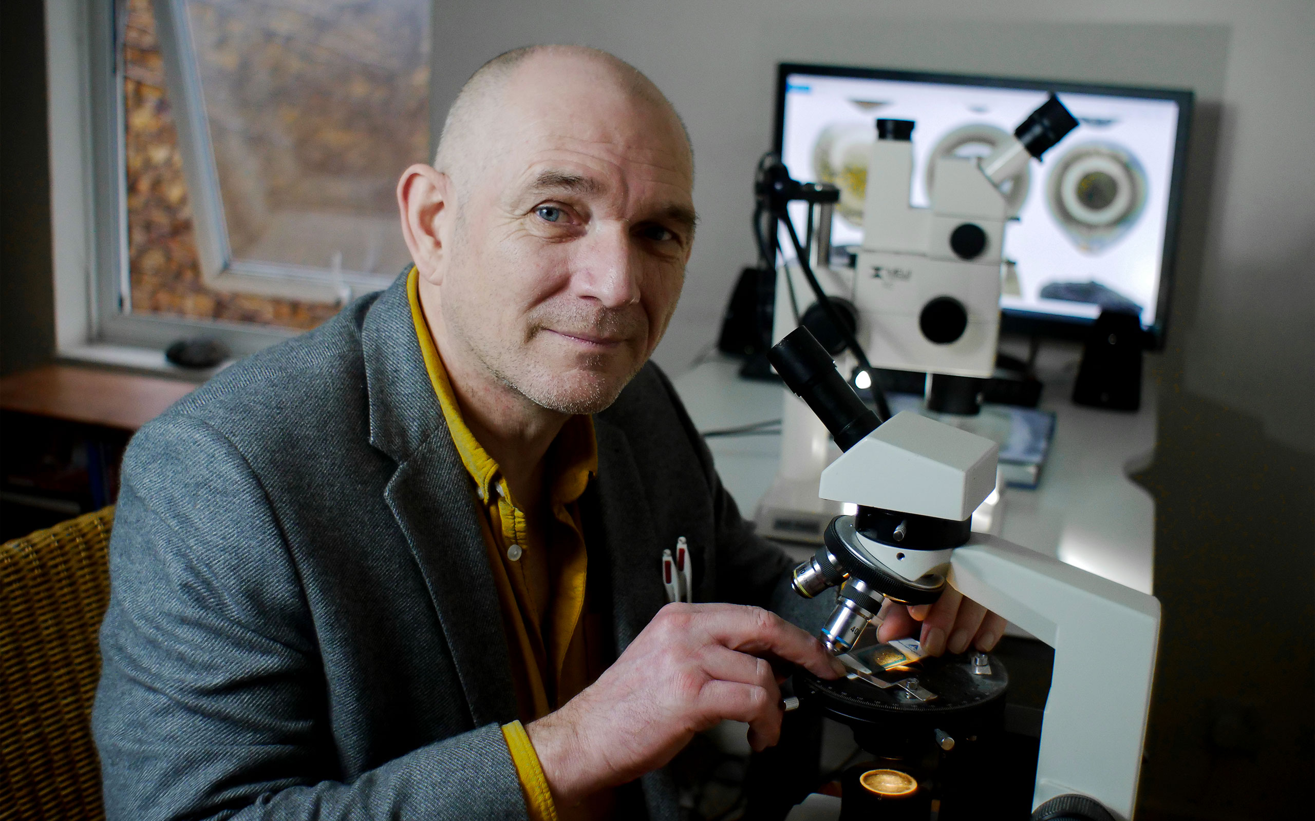 Matthew Genge in a yellow shirt and gray jacket seated at a microscope.