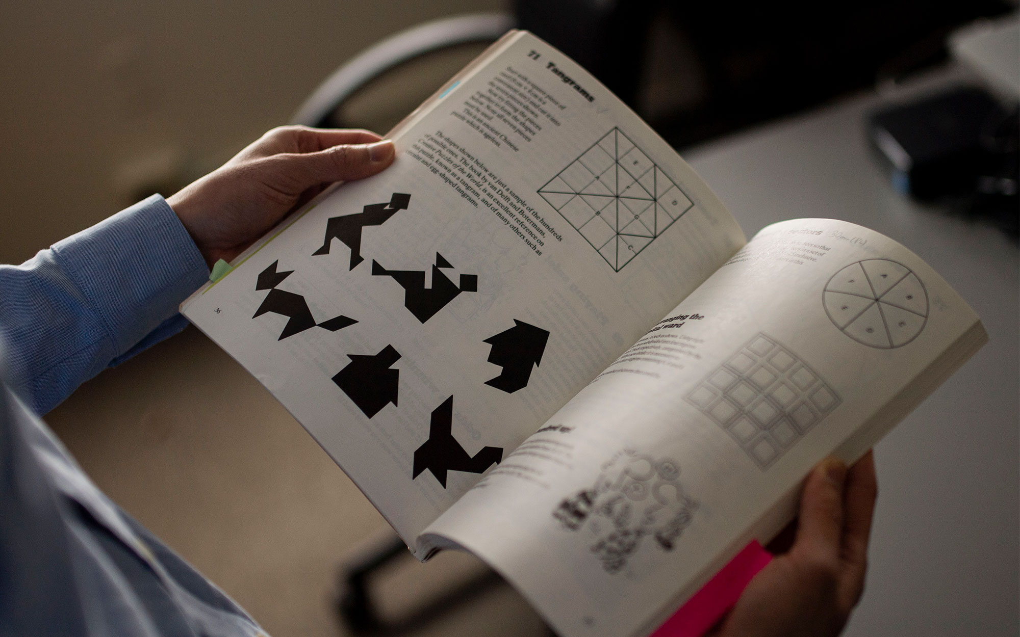 On the left, a close-up of Po-Shen Loh's hands holding open a book of math puzzles. On the right, the front cover of the book.
