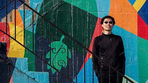 Po-Shen Loh standing on a stairway in front of a colored wall outside of his office in Pittsburgh.