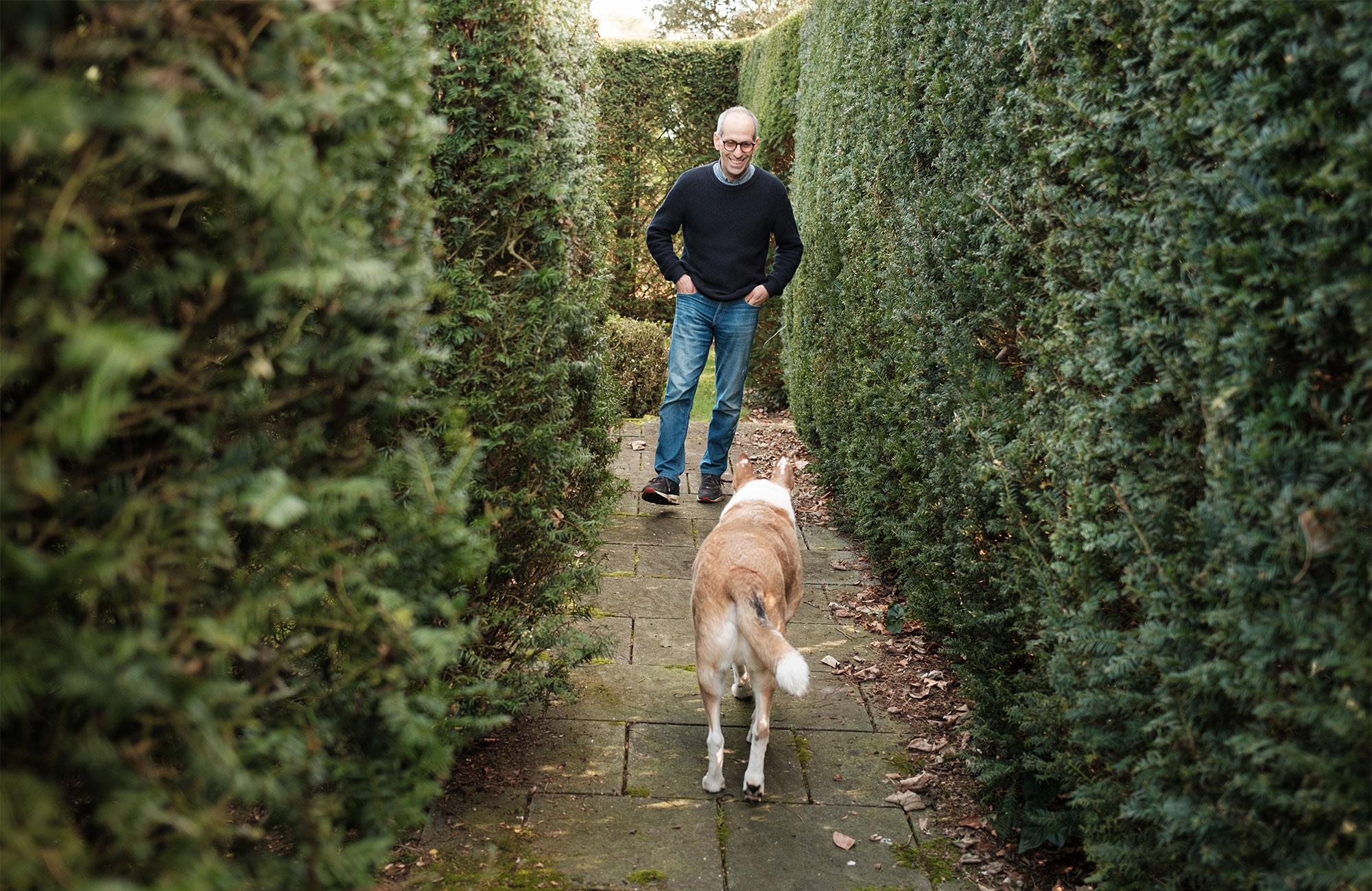 Arik Kershenbaum and his dog standing in a narrow path between tall hedges.