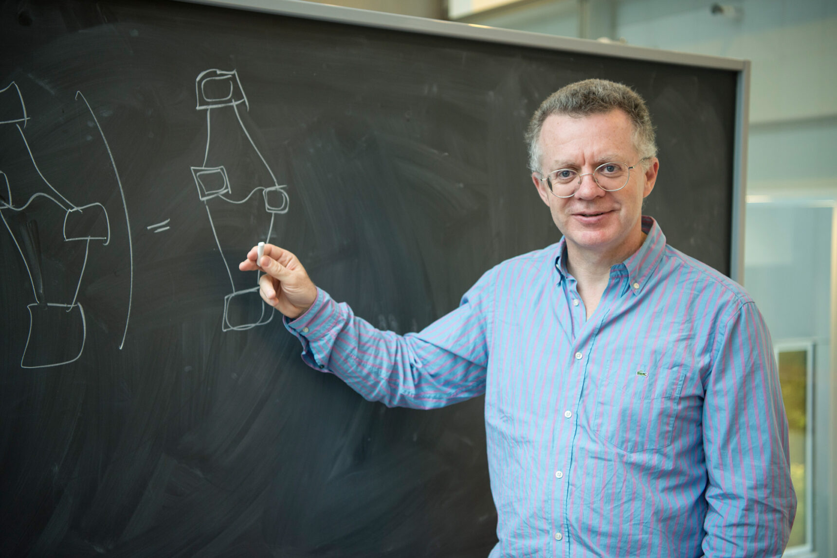 A man with curly gray hair and wireframe glasses smiles for the camera while holding a piece of chalk up to a blackboard.