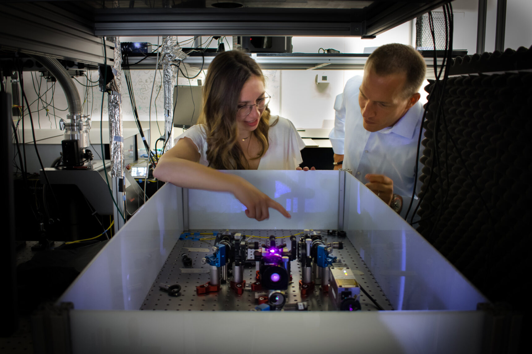A man and woman lean over an optical table; violet laser light can be seen bouncing between some mirrors.