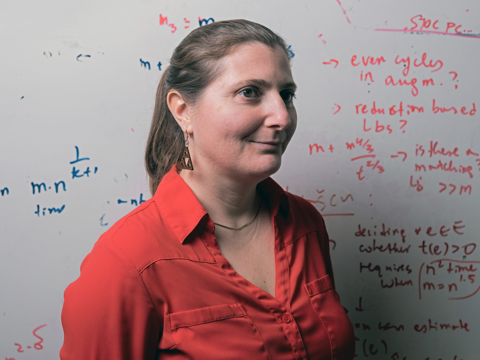 A color photo Virginia Williams in a red shirt in front of a whiteboard, and a color photo of Josh Alman in a gray shirt with a gray background