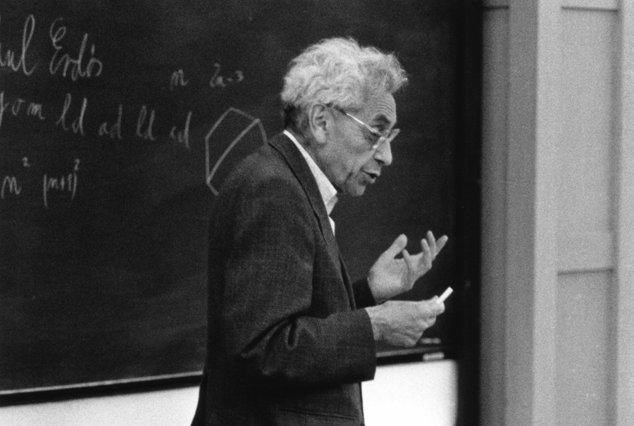 Black-and-white photo of Paul Erdős in front of a chalkboard; black-and-white photo of András Hajnal seated indoors