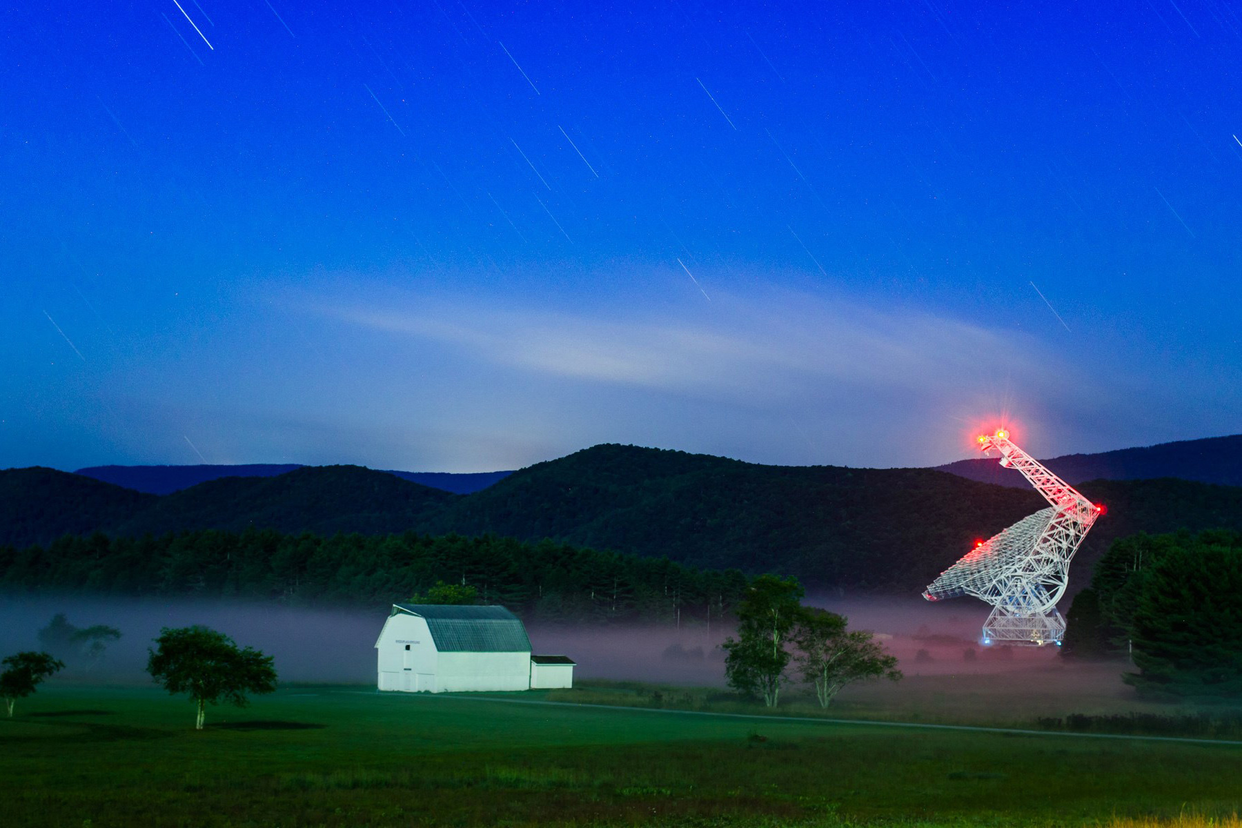 Photo with the Green Bank Telescope at right and a barnhouse at left, set in front of green mountains and a blue sky