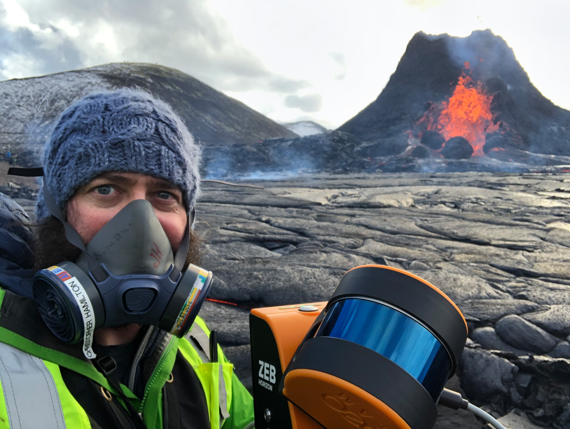 A man in a mask holding a LIDAR instrument in front of a volcano.