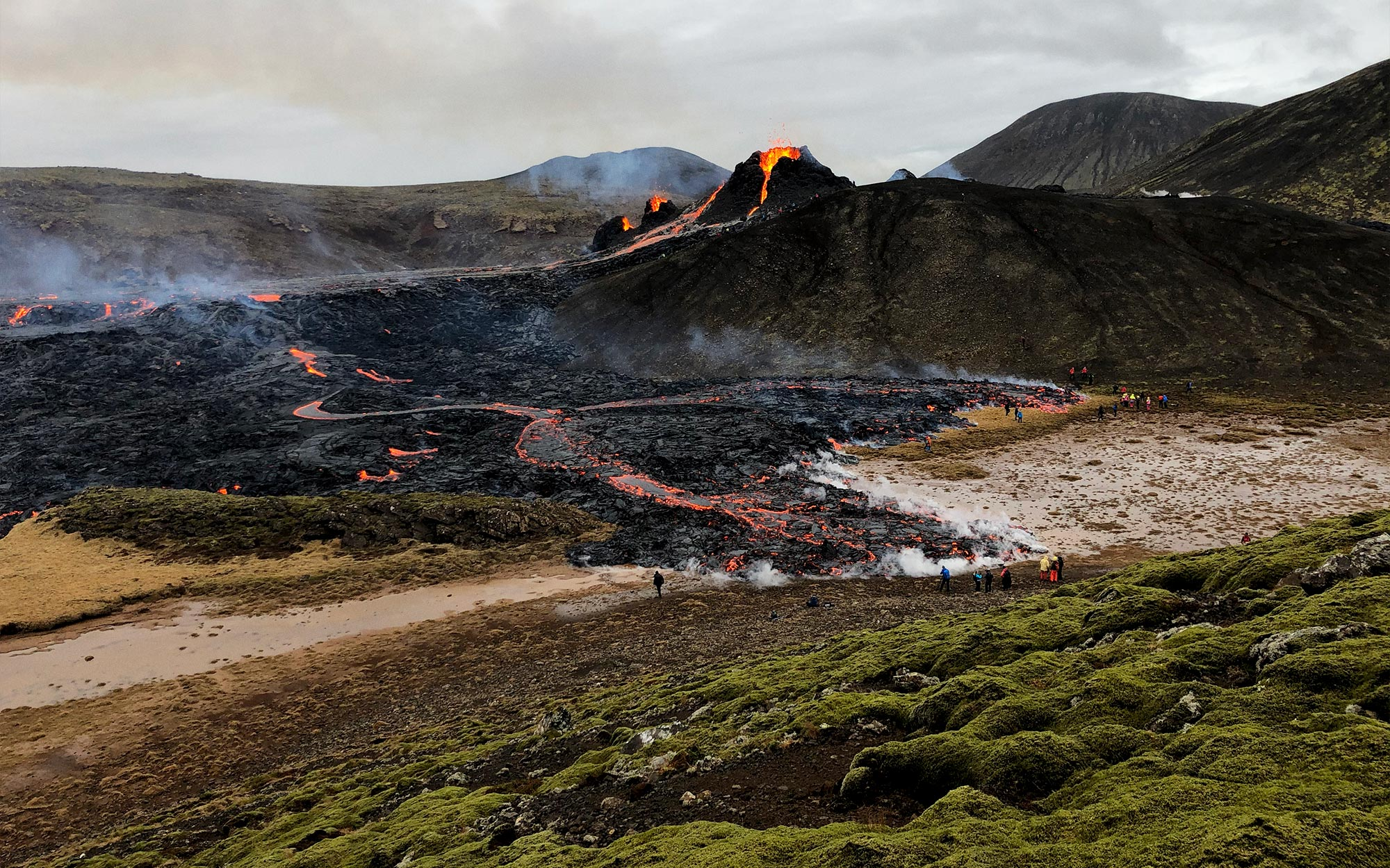 A volcano with orange lava flows coming down into a valley, with about 20 people standing at the base.