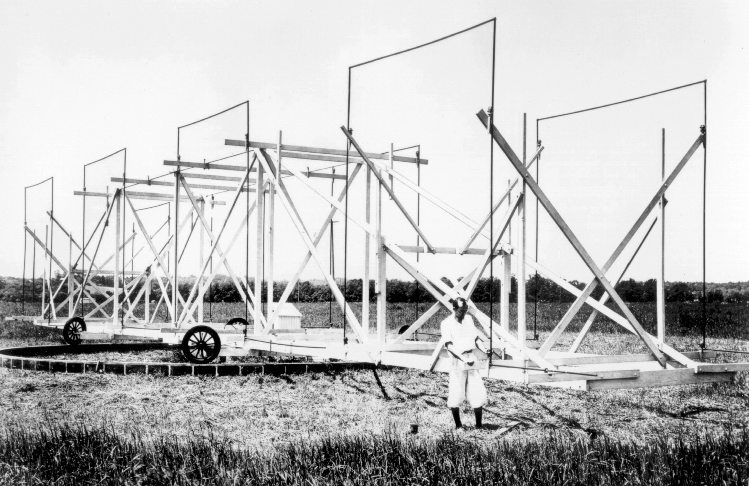"Black and white photo of Karl Janksy in a field in front of the device nicknamed ""Jansky's merry-go-round"""