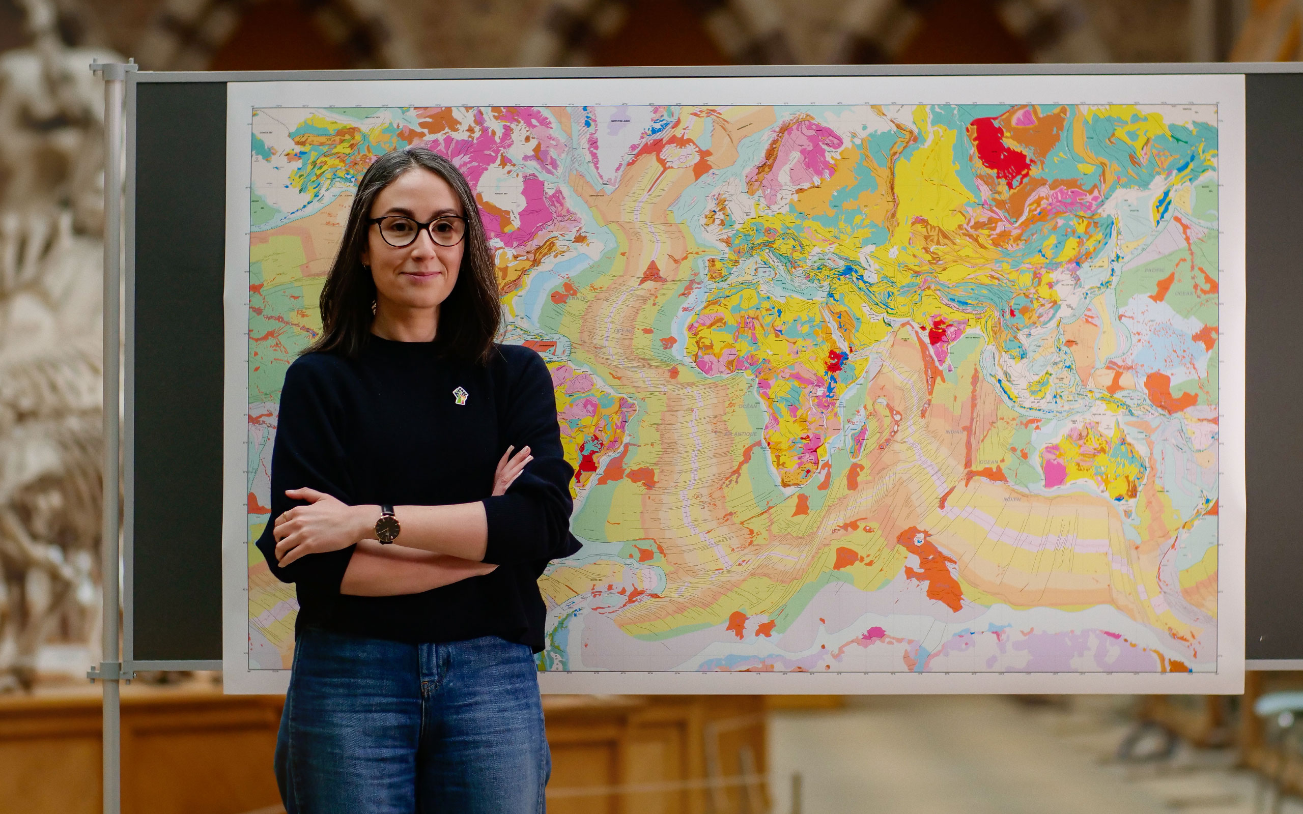 A woman in front of a pastel-colored map.