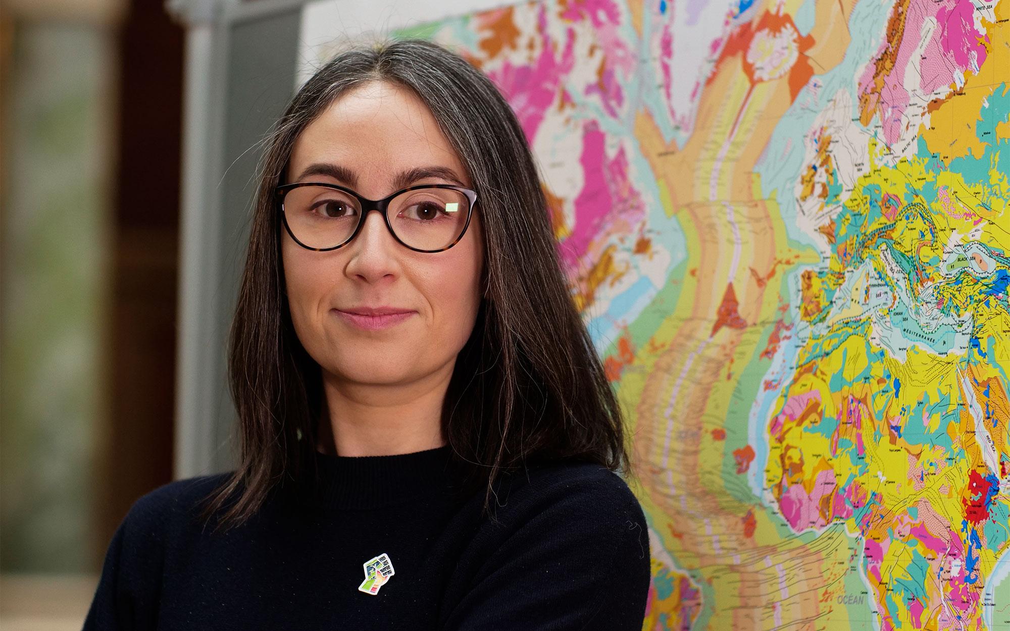 Lucía Pérez-Díaz in front of a map.