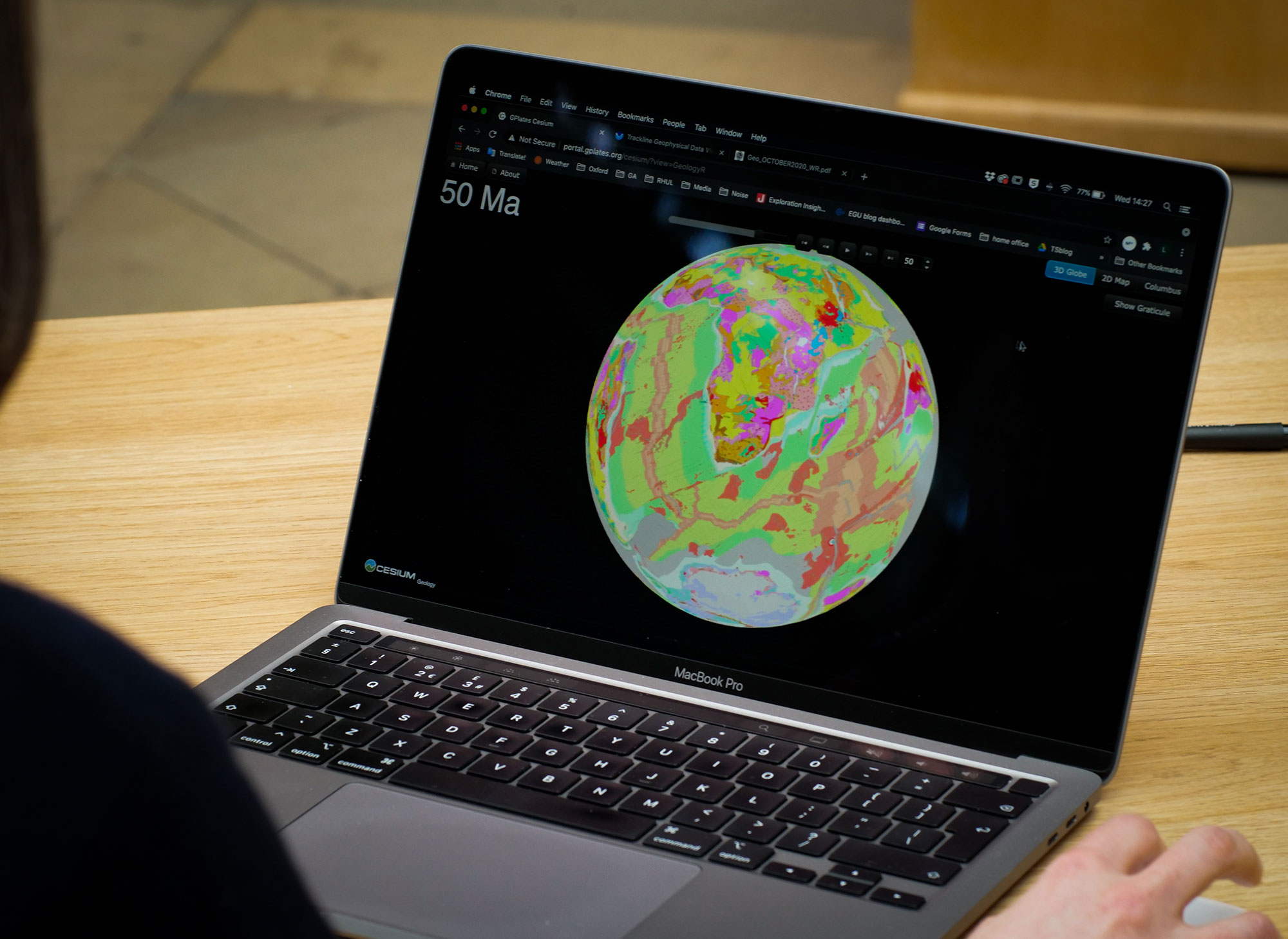 A laptop screen showing a colorful map of Earth.