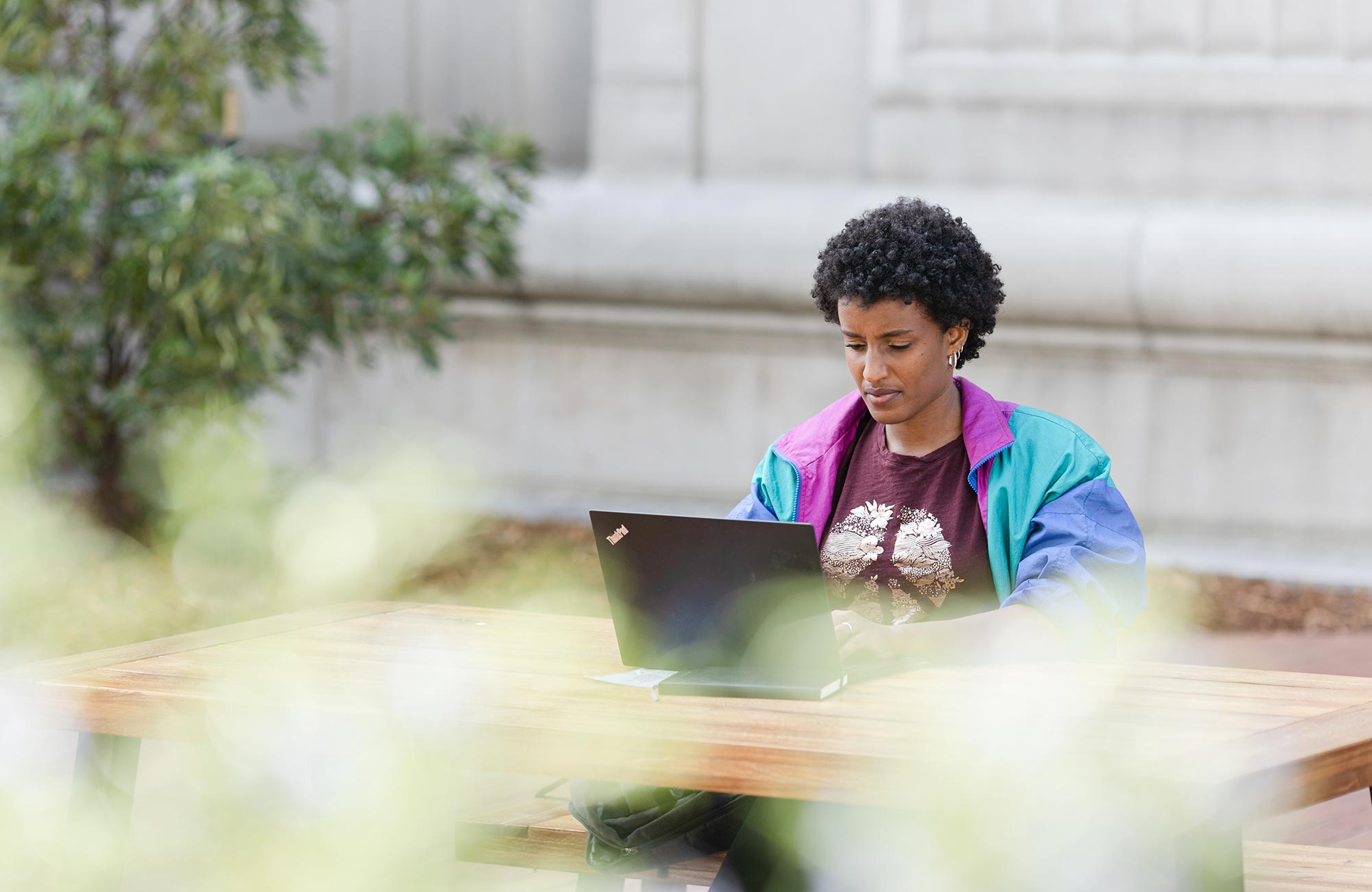 A diptych. On the left, Rediet Abebe sitting outside working on a laptop. On the right, a close-up of Abebe's laptop screen showing an article on increasing the presence of Black people in the field of artificial intelligence.