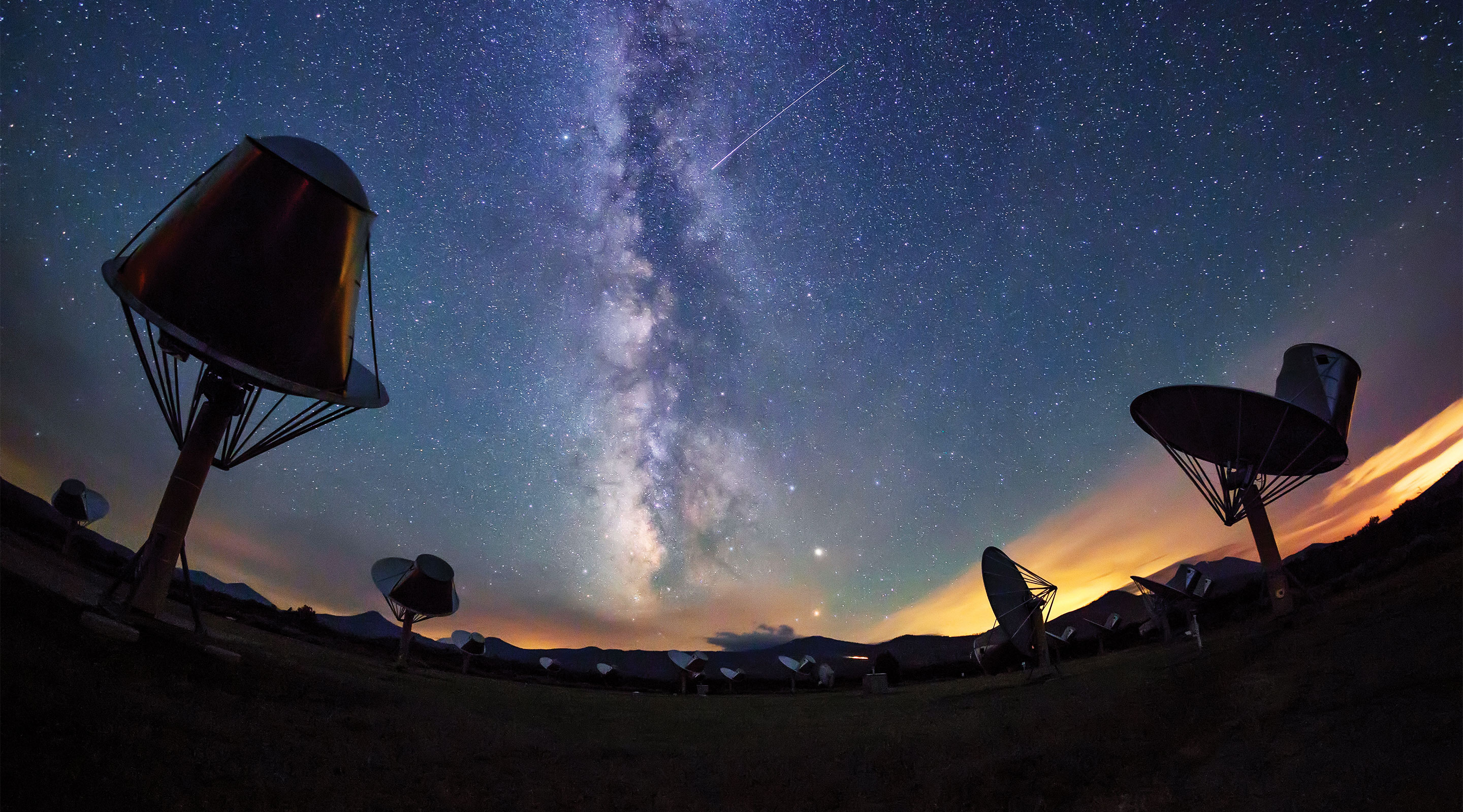 Photo of radio telescopes at the Allen Telescope Array with a starry sky featuring the Milky Way in the background.