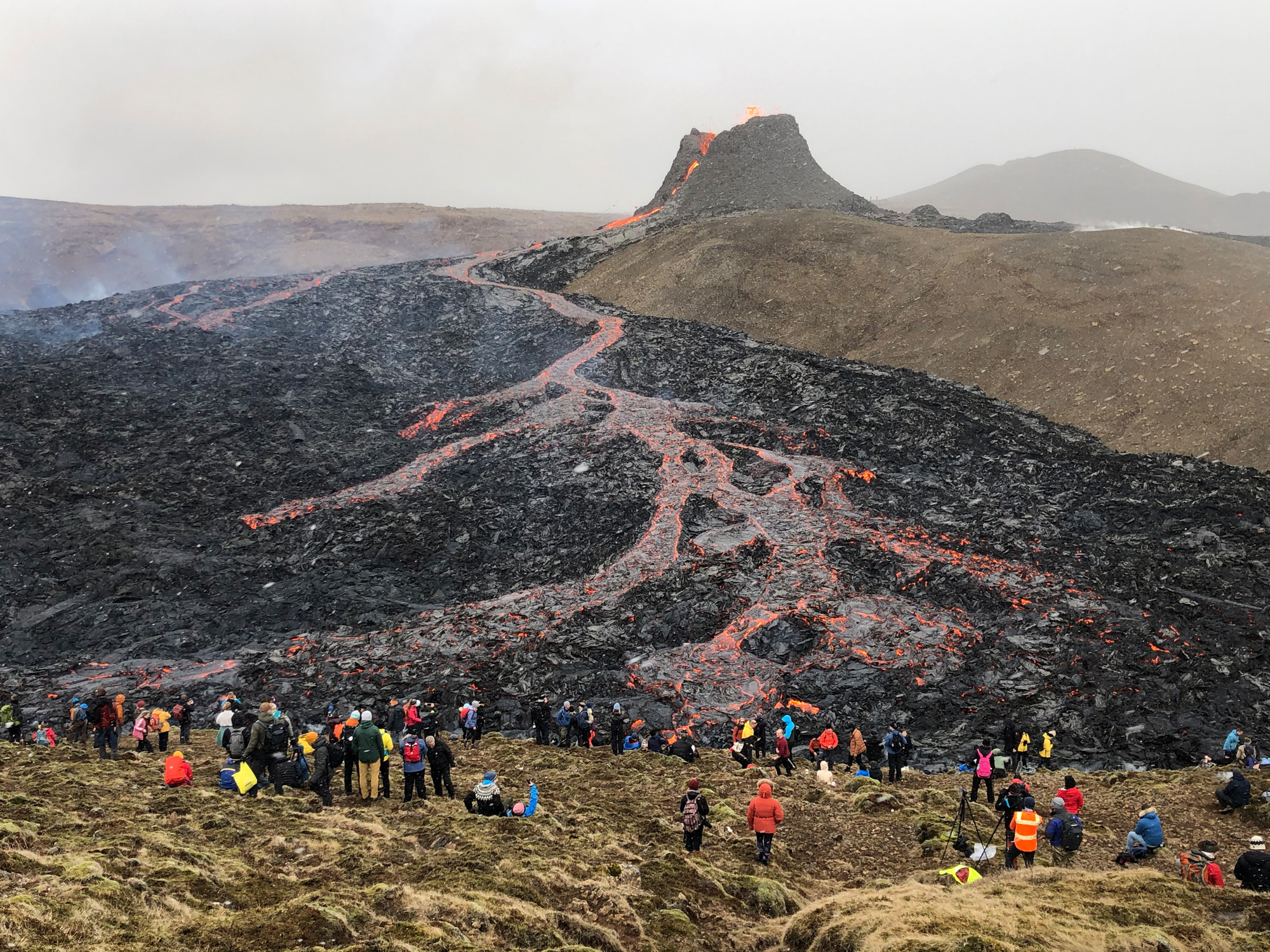Onlookers staring at a lava flow.