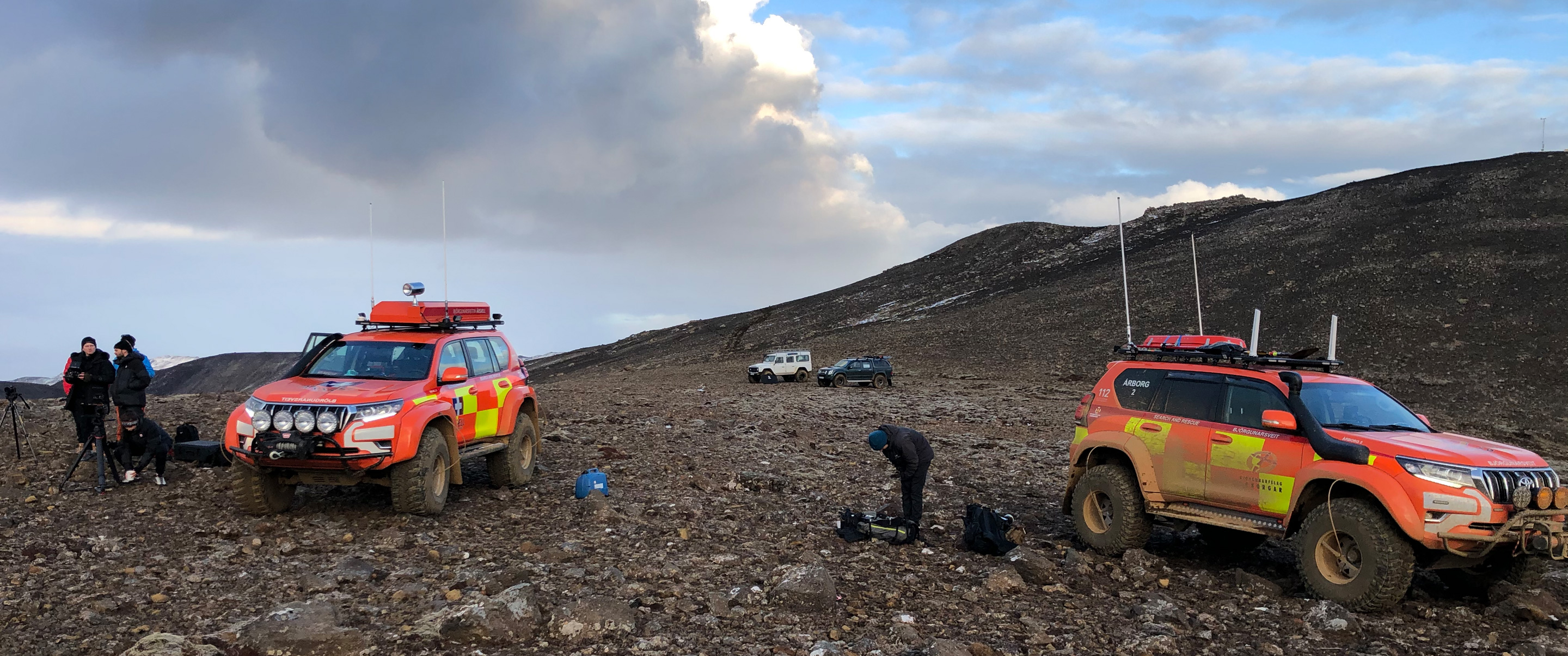 Two bright orange off-road vehicles on a lava field.