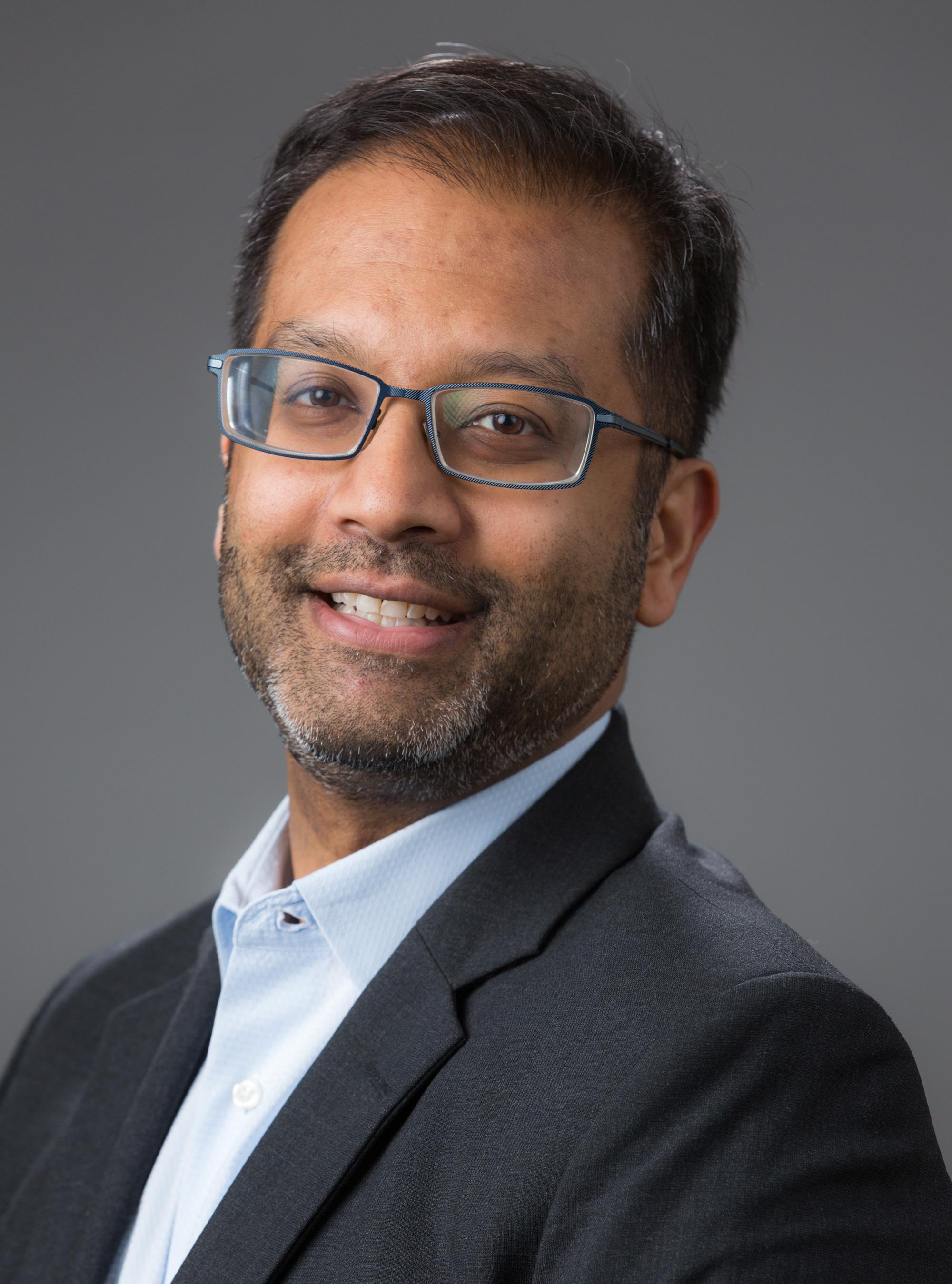 Samit Dasgupta in a suit jacket against a dark background
