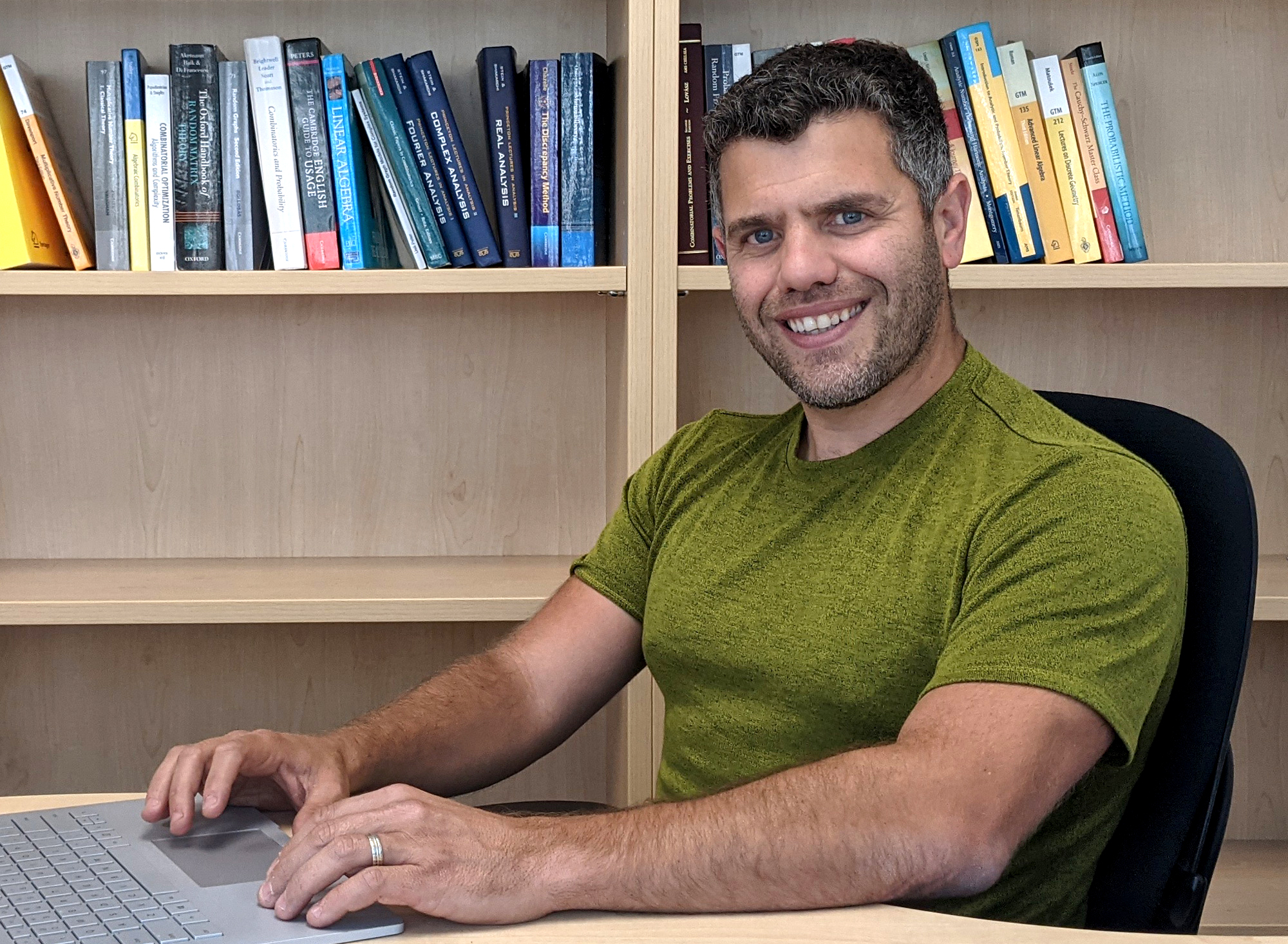 An outdoor photo of Michael Krivelevich in a purple shirt; a photo of Asaf Ferber in a green shirt sitting at a laptop