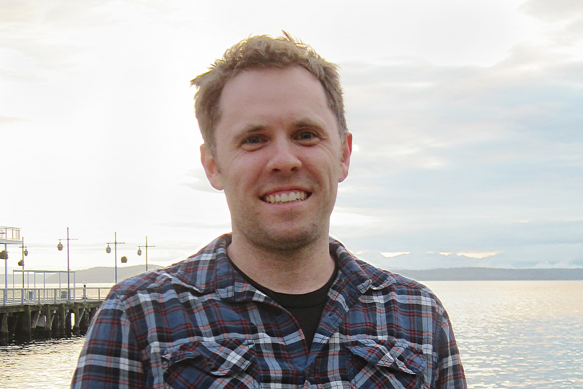 A man with a checked shirt standing in front of the water. A man with round glasses and a grey shirt.